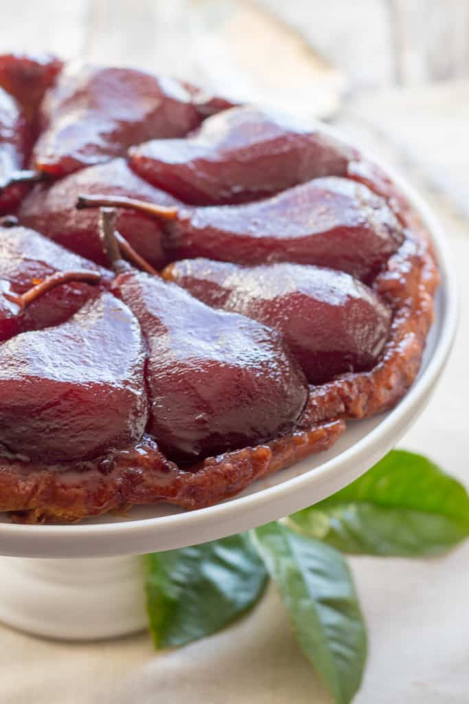 Close up of red wine pears baked in a tart on a cake stand.