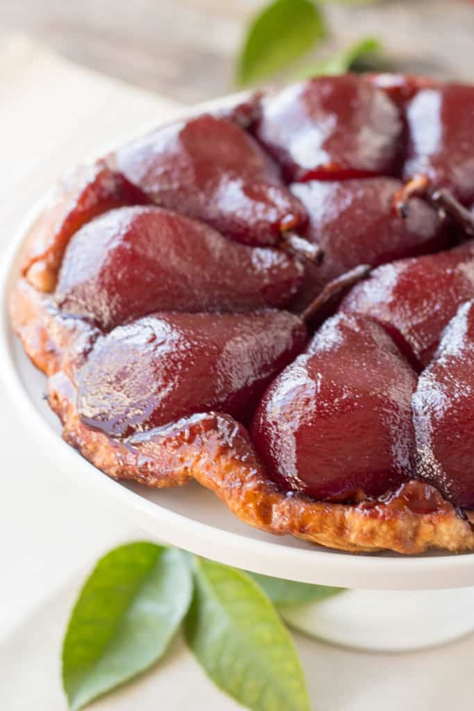 Close up of poached pear halves baked into a crust on a white dish.