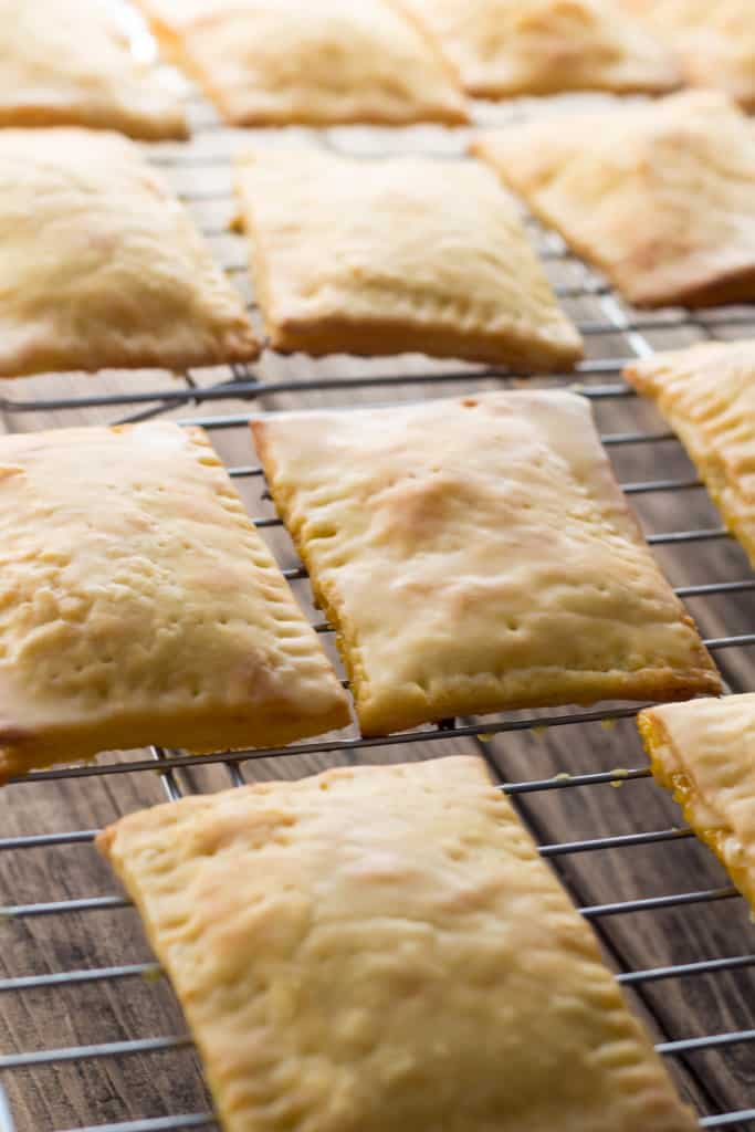 Baked passion fruit pop tarts on a wire cooling rack.
