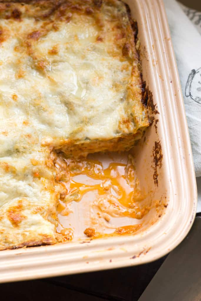 Top view of a baking dish of lasagna missing the corner slice.