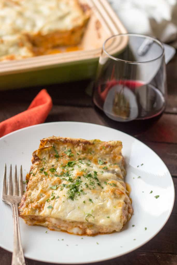 A slice of lasagna bolognese sprinkled with fresh herbs on a white plate with a fork and a red wine glass.