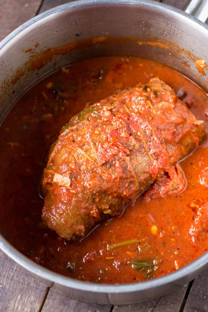 A beef braciole in a Dutch oven of tomato sauce.