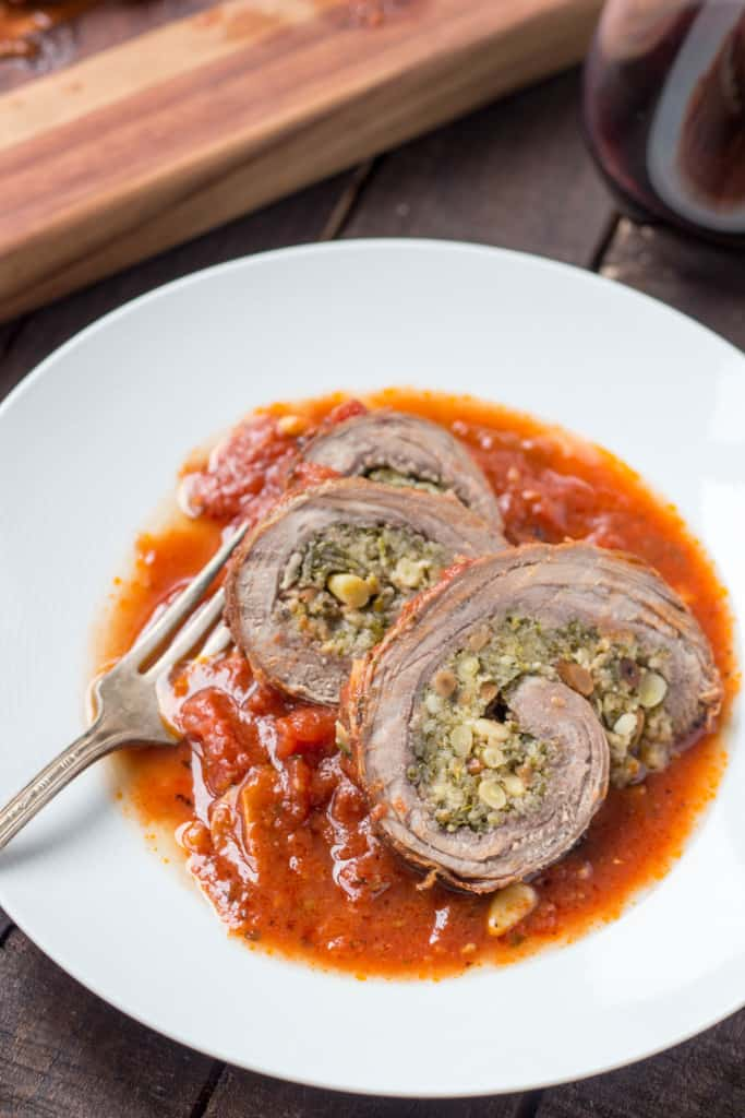 Close up of three slices of Italian Braciole in a white bowl with a fork.