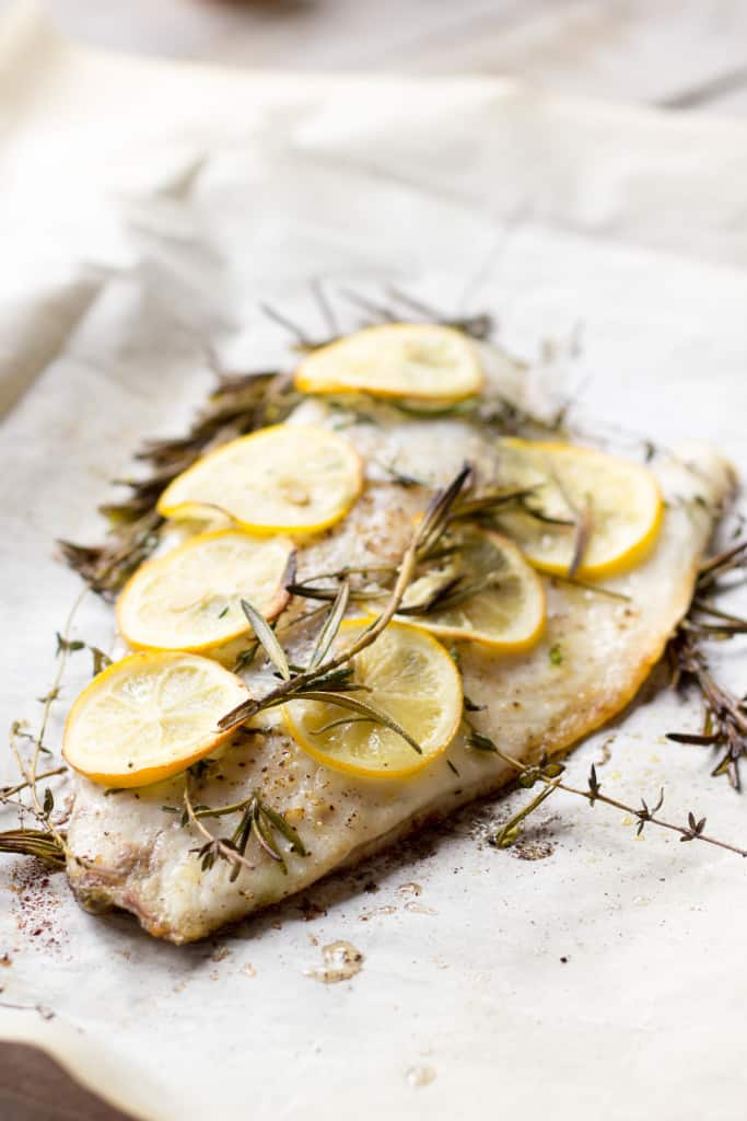 A roasted barramundi fillet covered with lemon rounds and sprigs of rosemary.