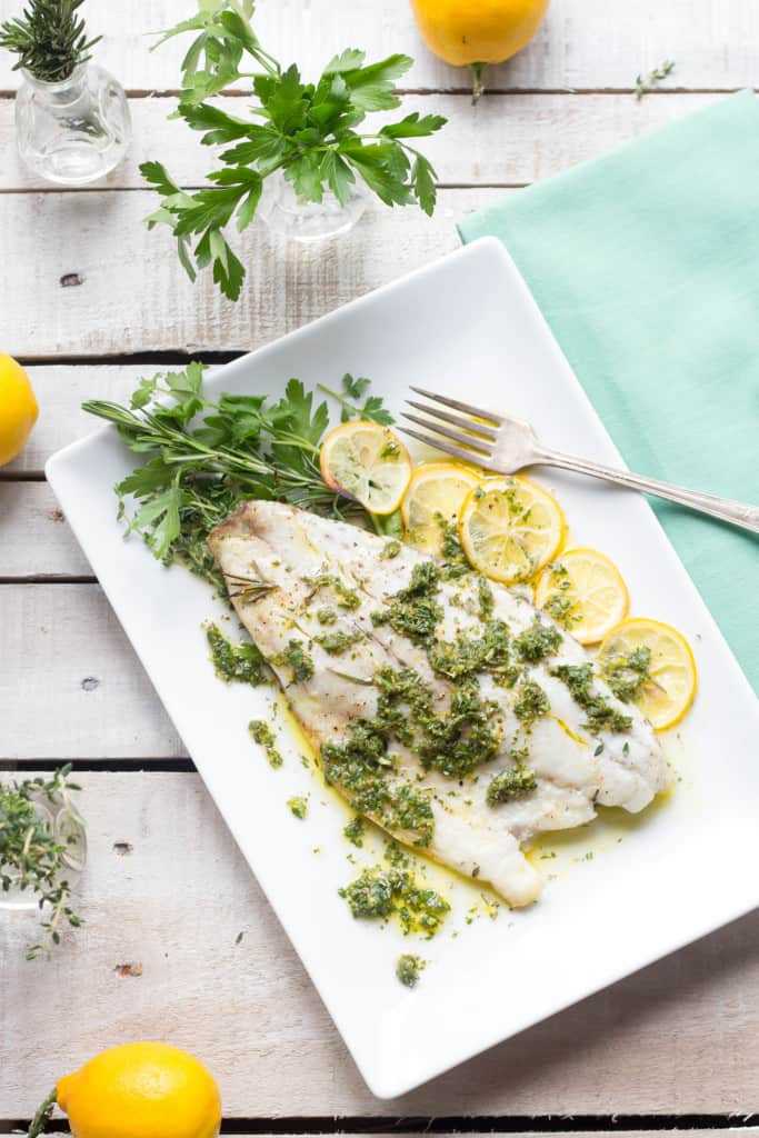 Top view of a rectangle serving platter with roasted barramundi and lemon slices.