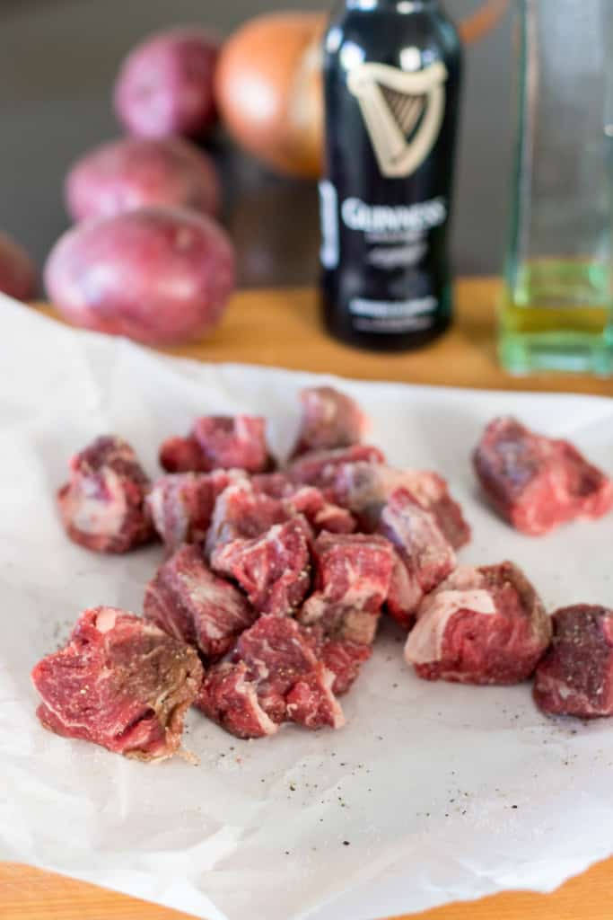 Fresh, raw beef stew meat cubes on butcher paper.