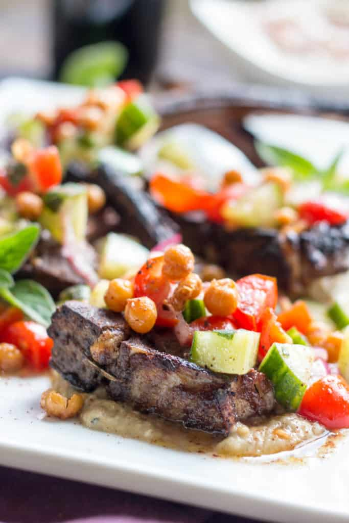 Side view of tomato cucumber salad and crispy chickpeas on top of a bone-in lamb chop.
