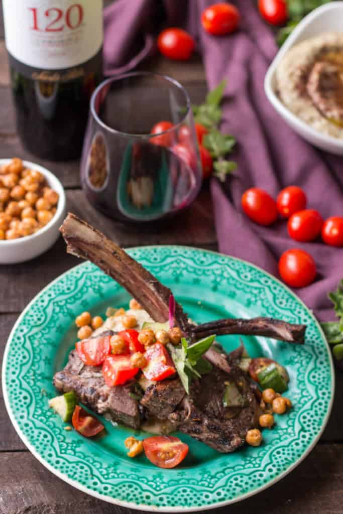 Two lamb chops crossed over eggplant puree and topped with tomato cucumber salad on a dinner plate.