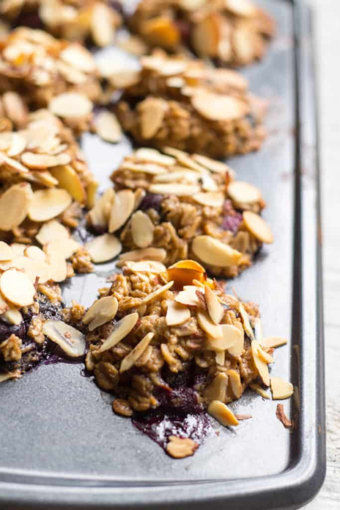 Close up of sliced almonds pressed into the tops of blueberry oatmeal cups in a muffin tin.