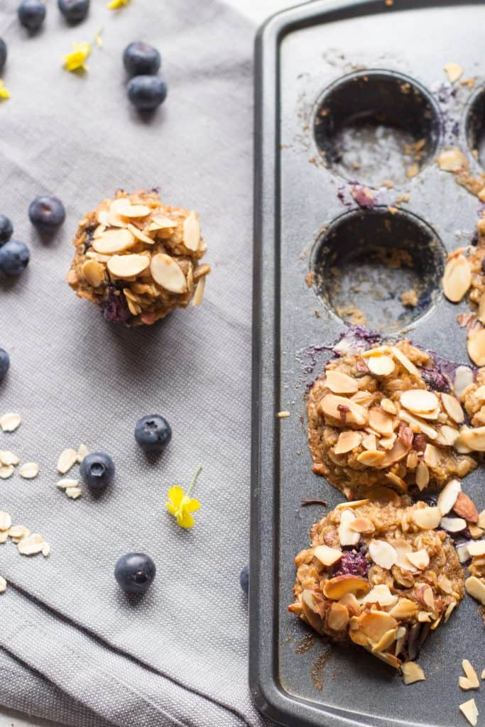 A blueberry oatmeal cup next to a muffin tin.