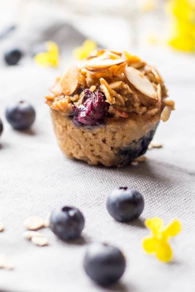 A close up of a single blueberry almond baked oatmeal cup on a cloth napkin.