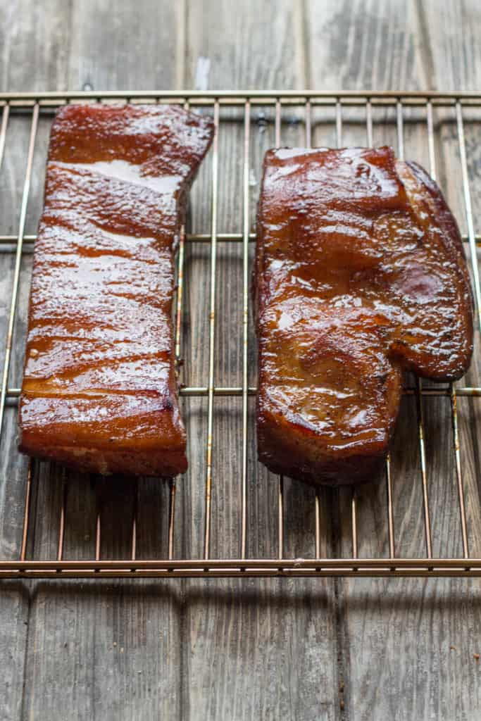 Top view of two slabs of smoked bacon on a wire rack.