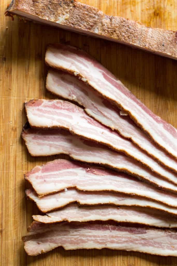 A wooden cutting board with thickly sliced bacon.