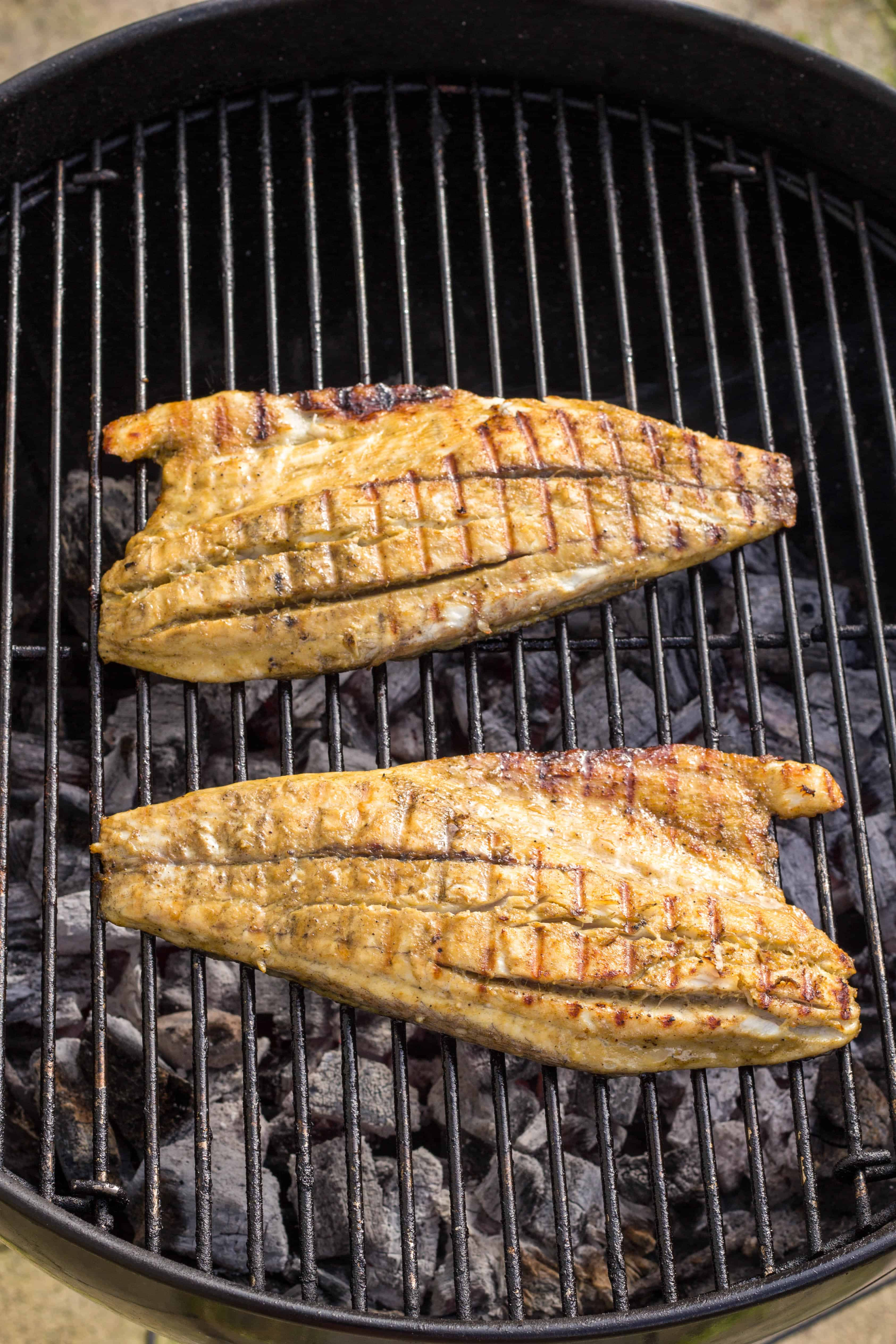 Two barramundi fillets on a charcoal grill.