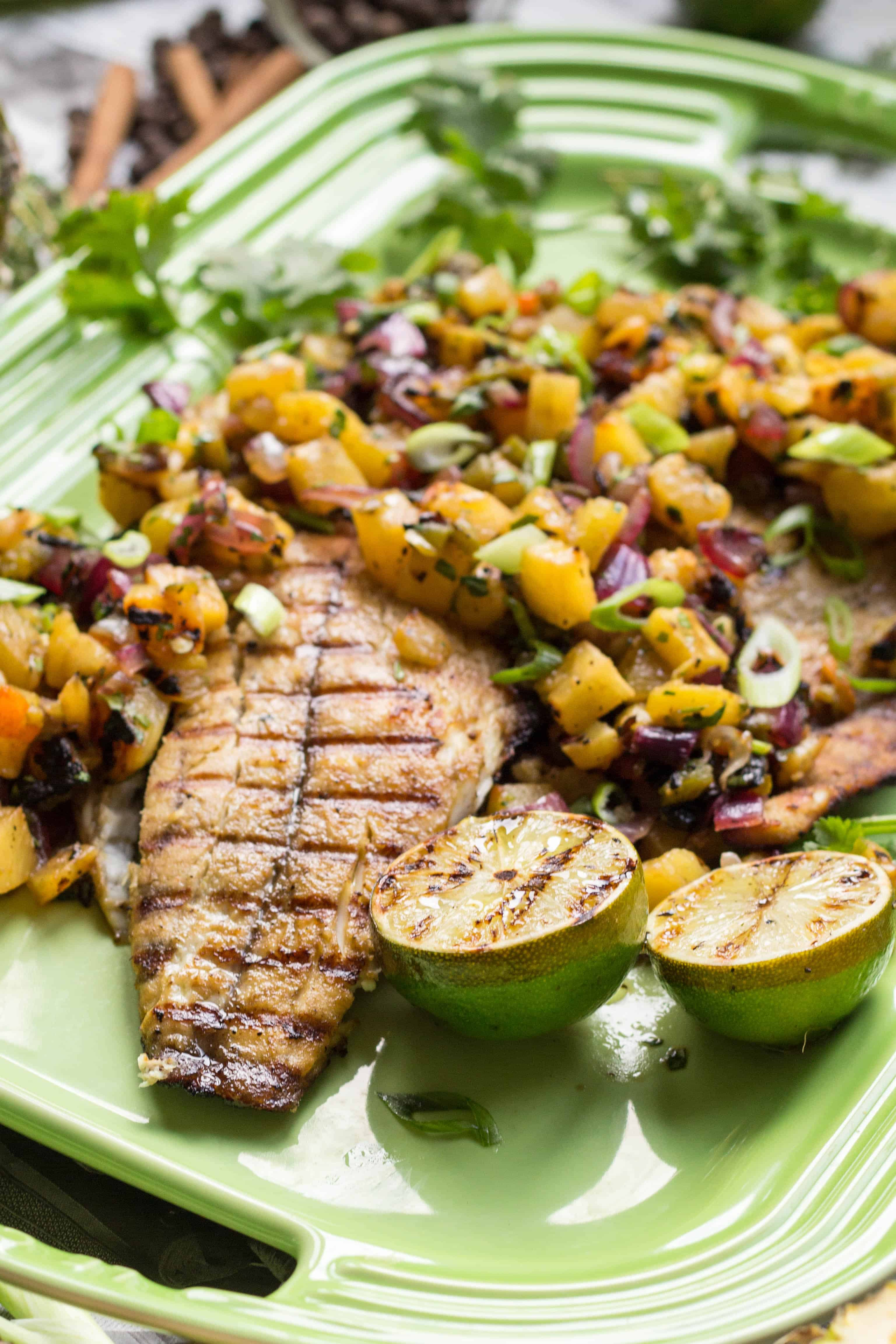 Serving platter with grilled barramundi, lime halves, and fresh pineapple salsa.