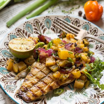 Close up of a dinner plate with a grilled barramundi fillet topped with fresh pineapple salsa.