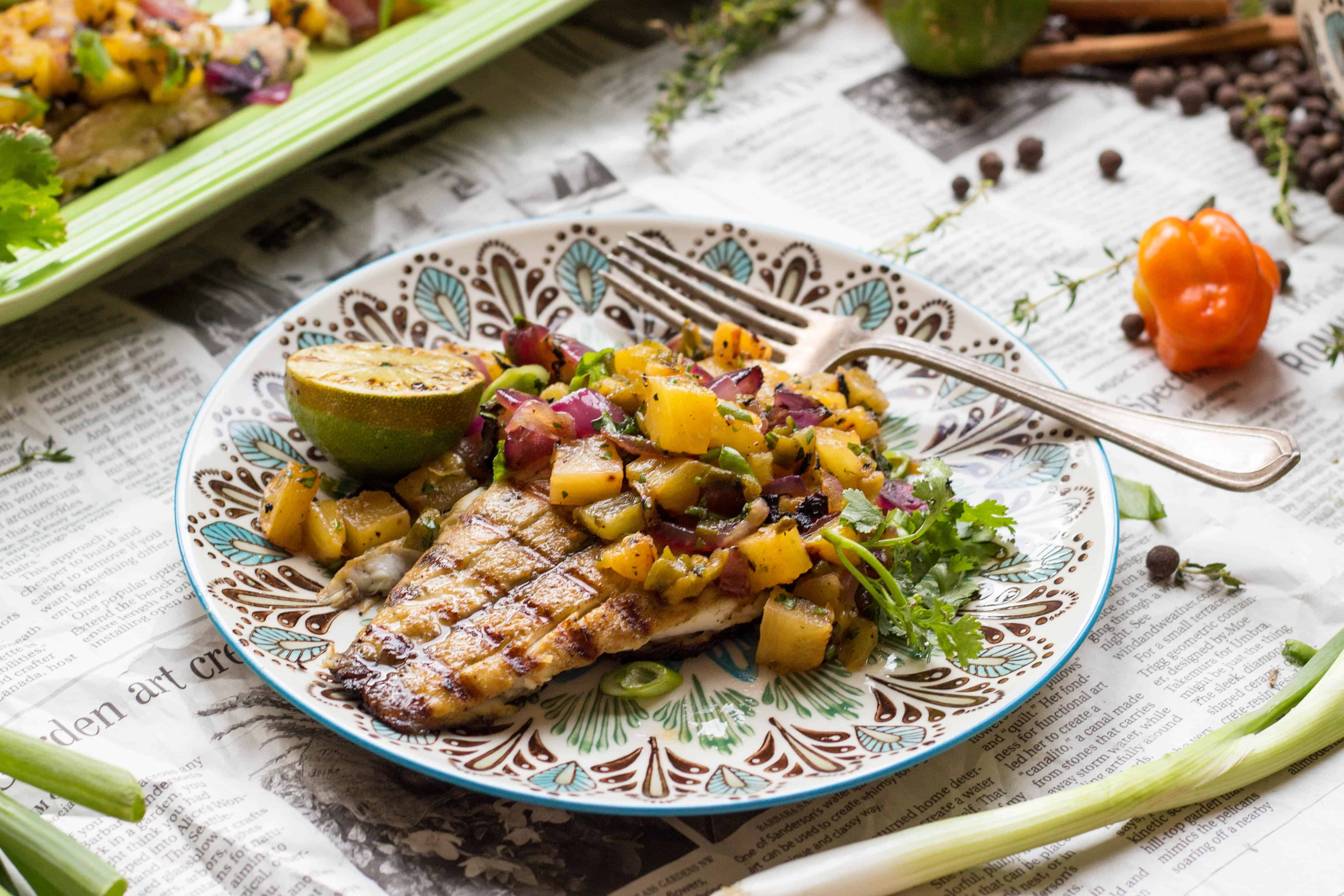 Patterned dinner plate and fork with a grilled barramundi fillet and fresh pineapple salsa with grilled limes.