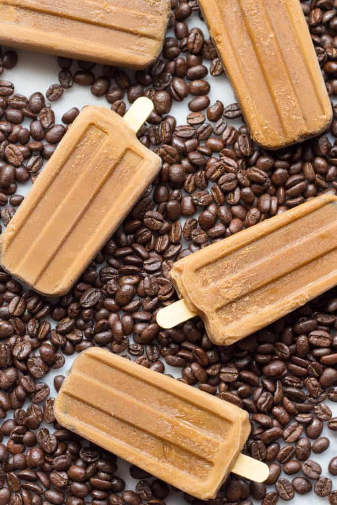Top view of Vietnamese coffee popsicles on a coffee-bean-covered tabletop.