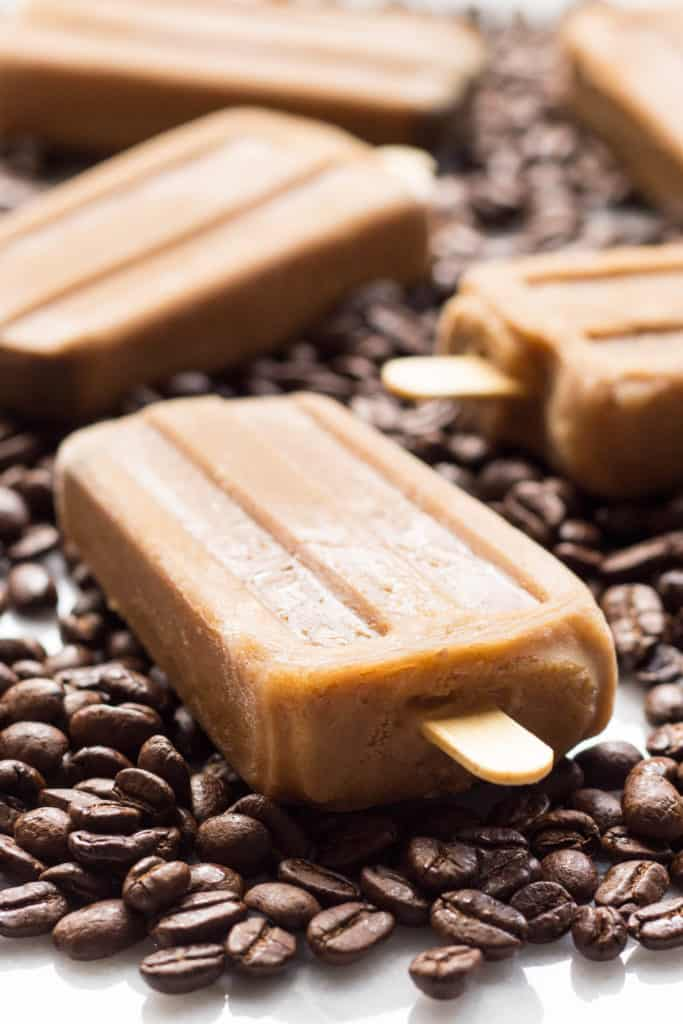 Close up of a Vietnamese coffee popsicle among coffee beans on a table.