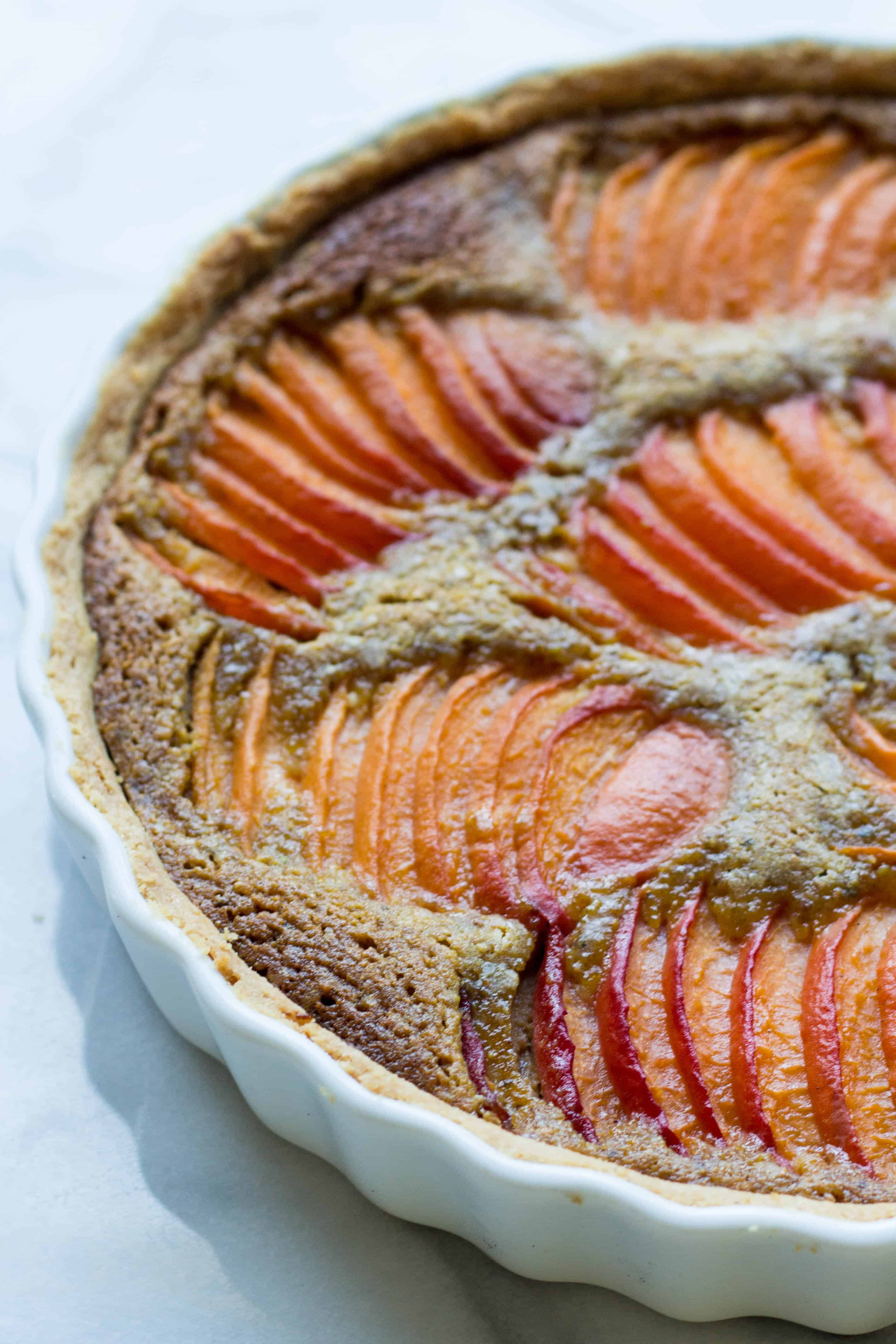 Close up top view of sliced apricots baked into a tart.