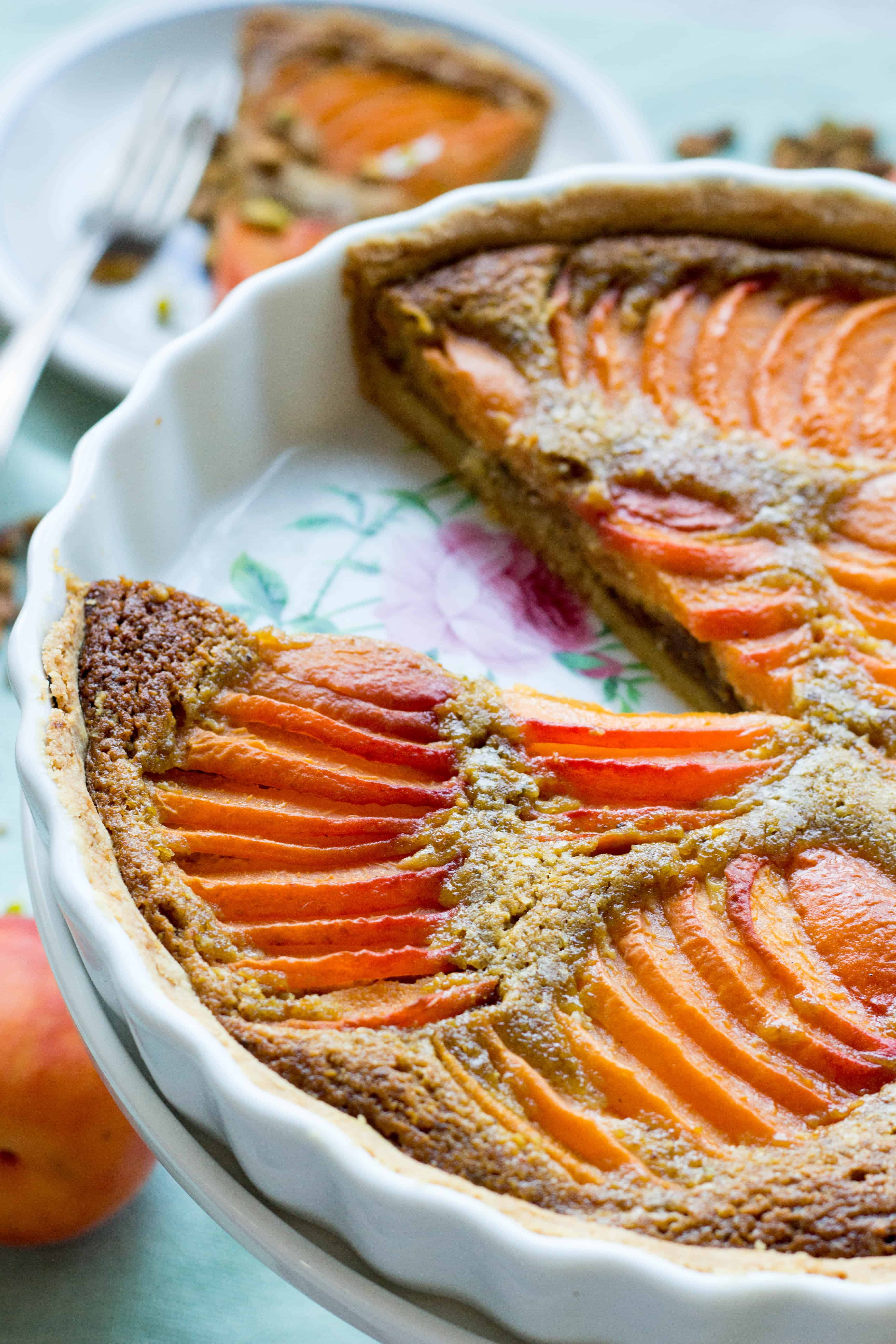 An apricot pistachio tart in a round baking dish with a slice missing.