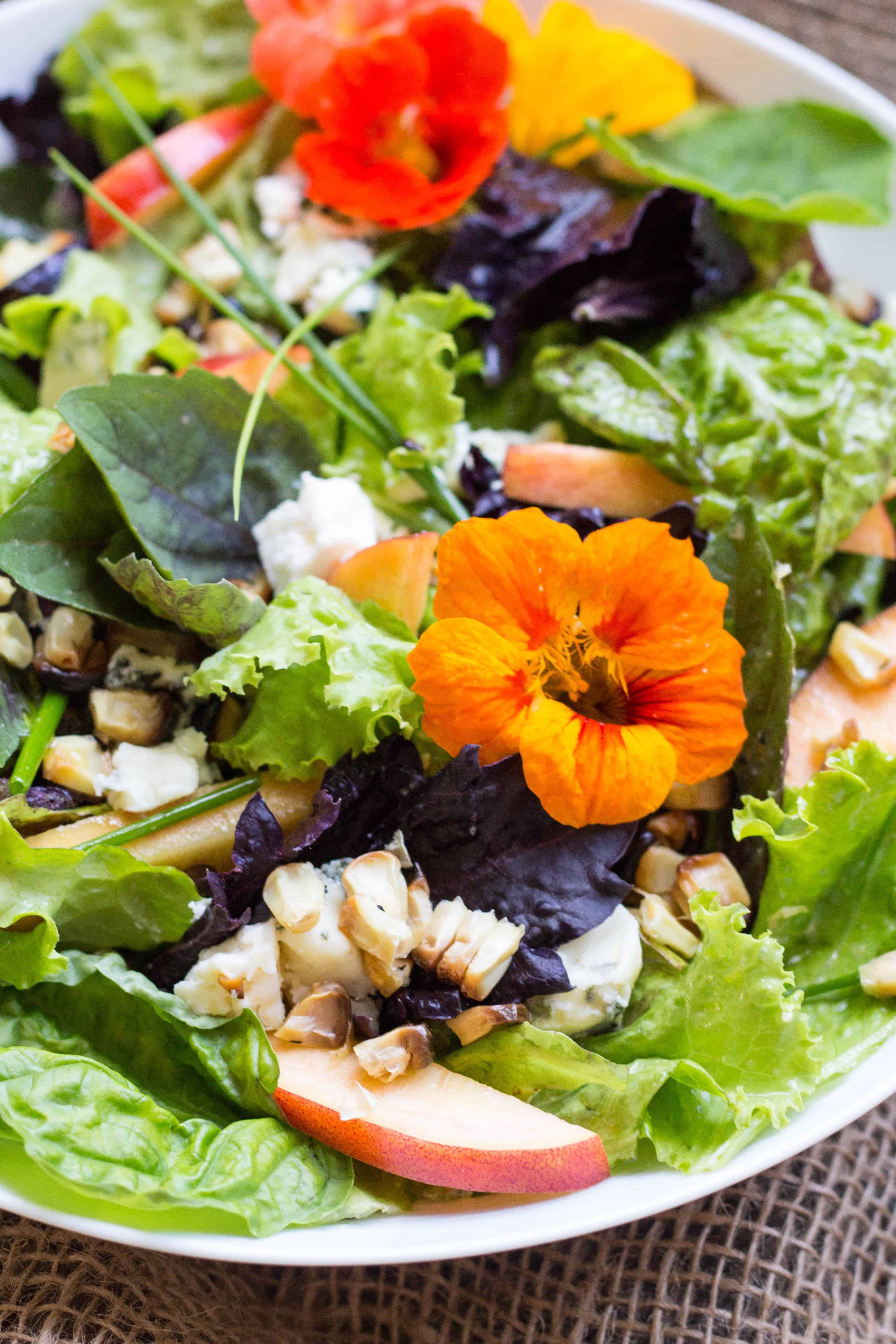Close up of edible flowers and sweet corn topping a leafy green salad.