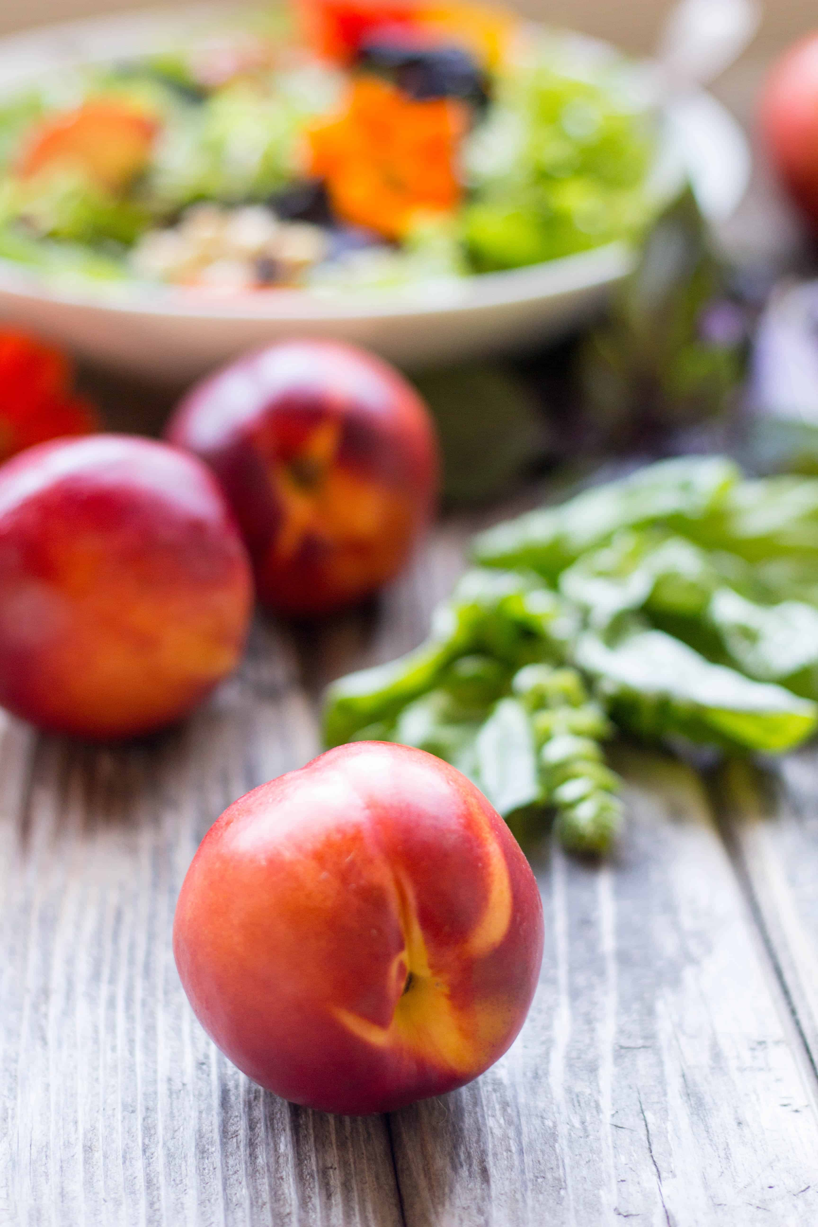 Fresh nectarines on a wood table.