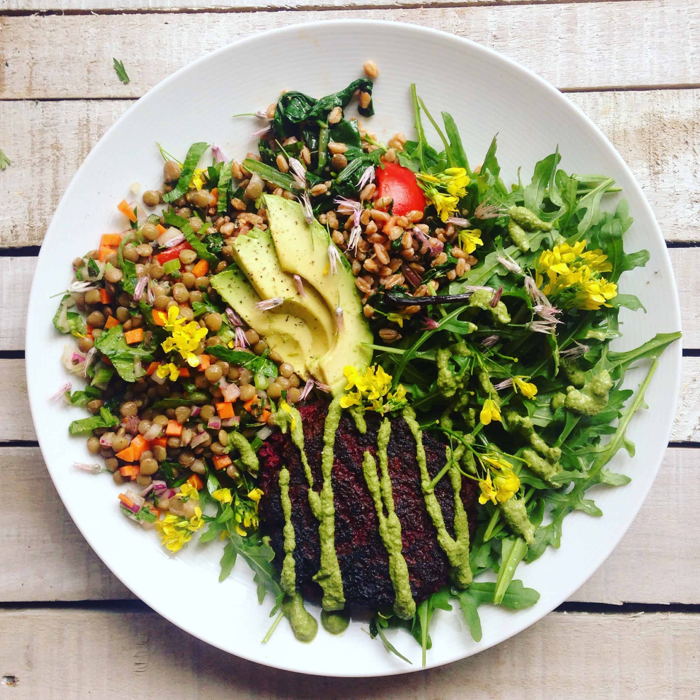 Top view of a large white plate with a green salad and avocado slices topped with a lentil beet burger.