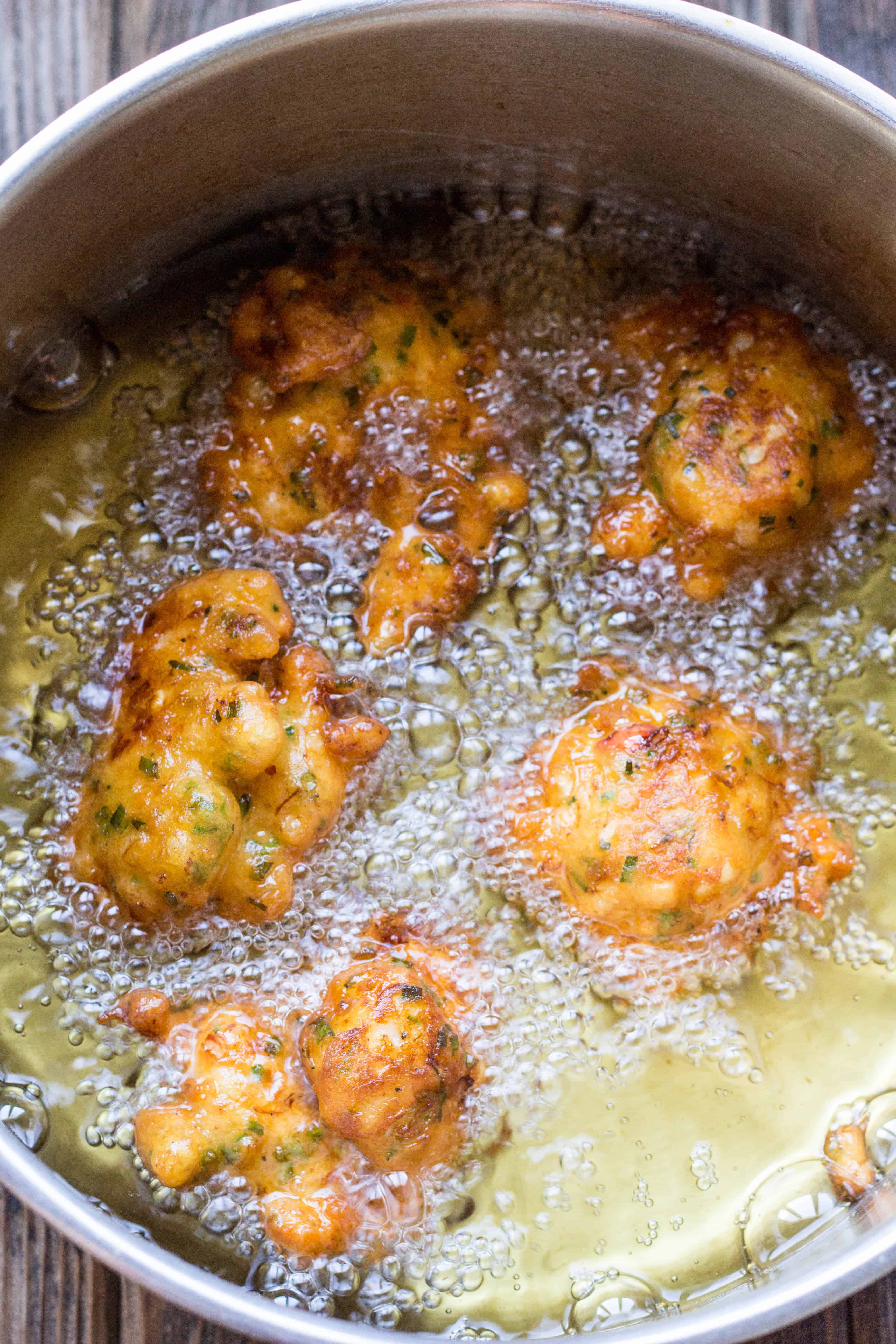 A skillet filled with oil bubbling around lobster corn fritters.