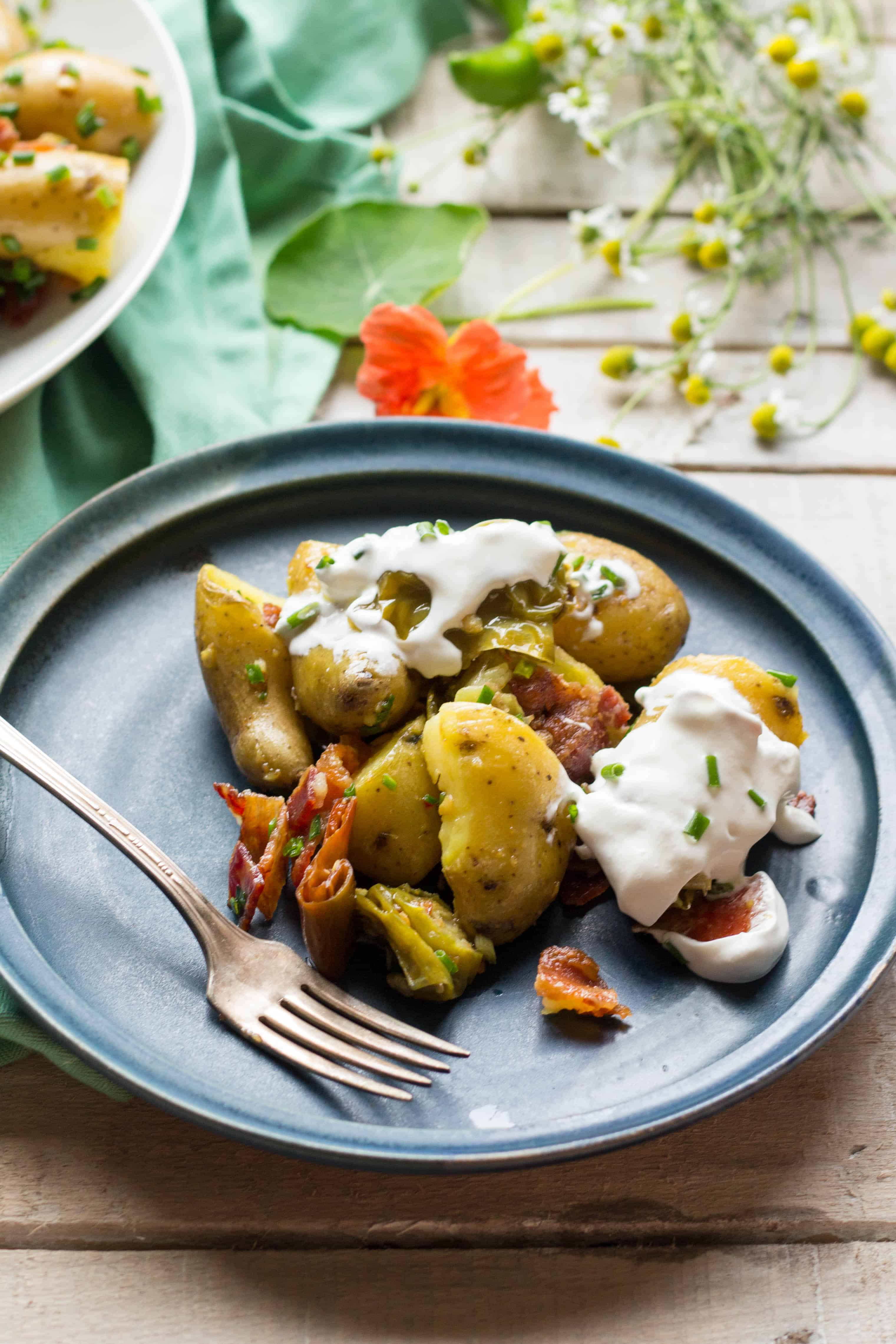 Warm golden potato salad with bacon and peppers on a blue dinner plate.