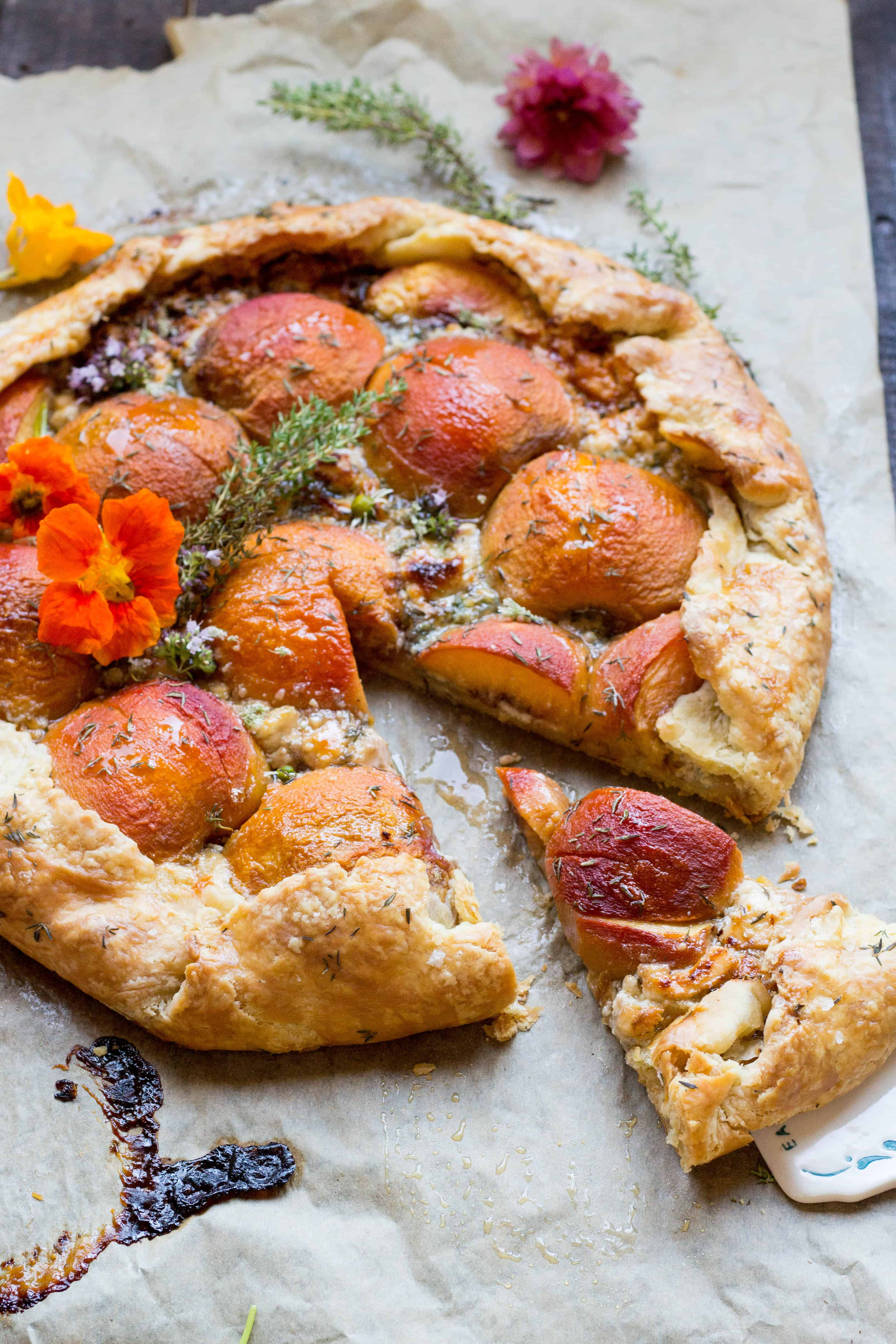 A slice cut out of a round savory peach galette.