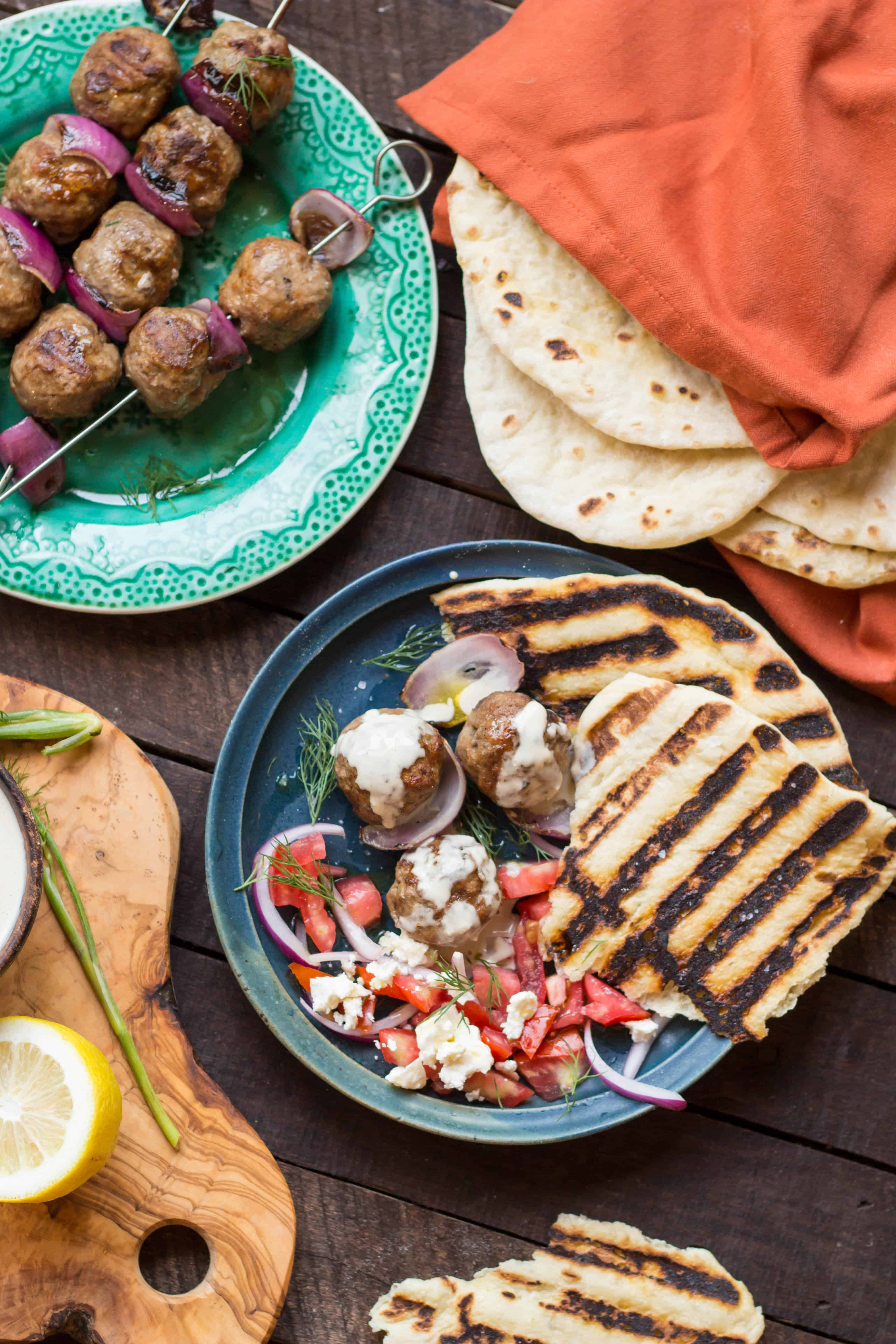 Table spread with lamb meatballs on skewers, a stack of a pita, and a dinner plate including tomato salad.