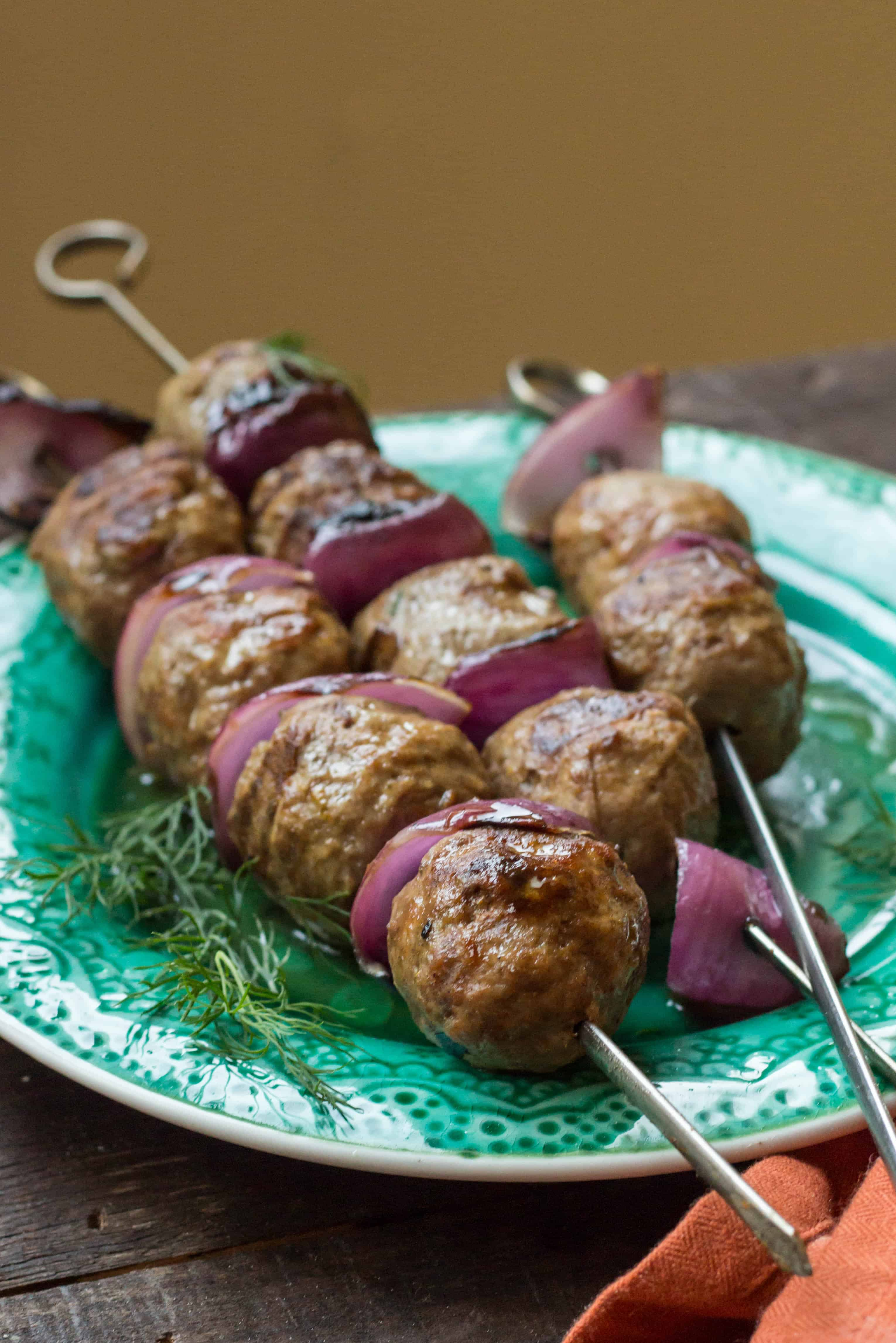 Lamb meatballs and red onion slices on metal skewers on a green plate.