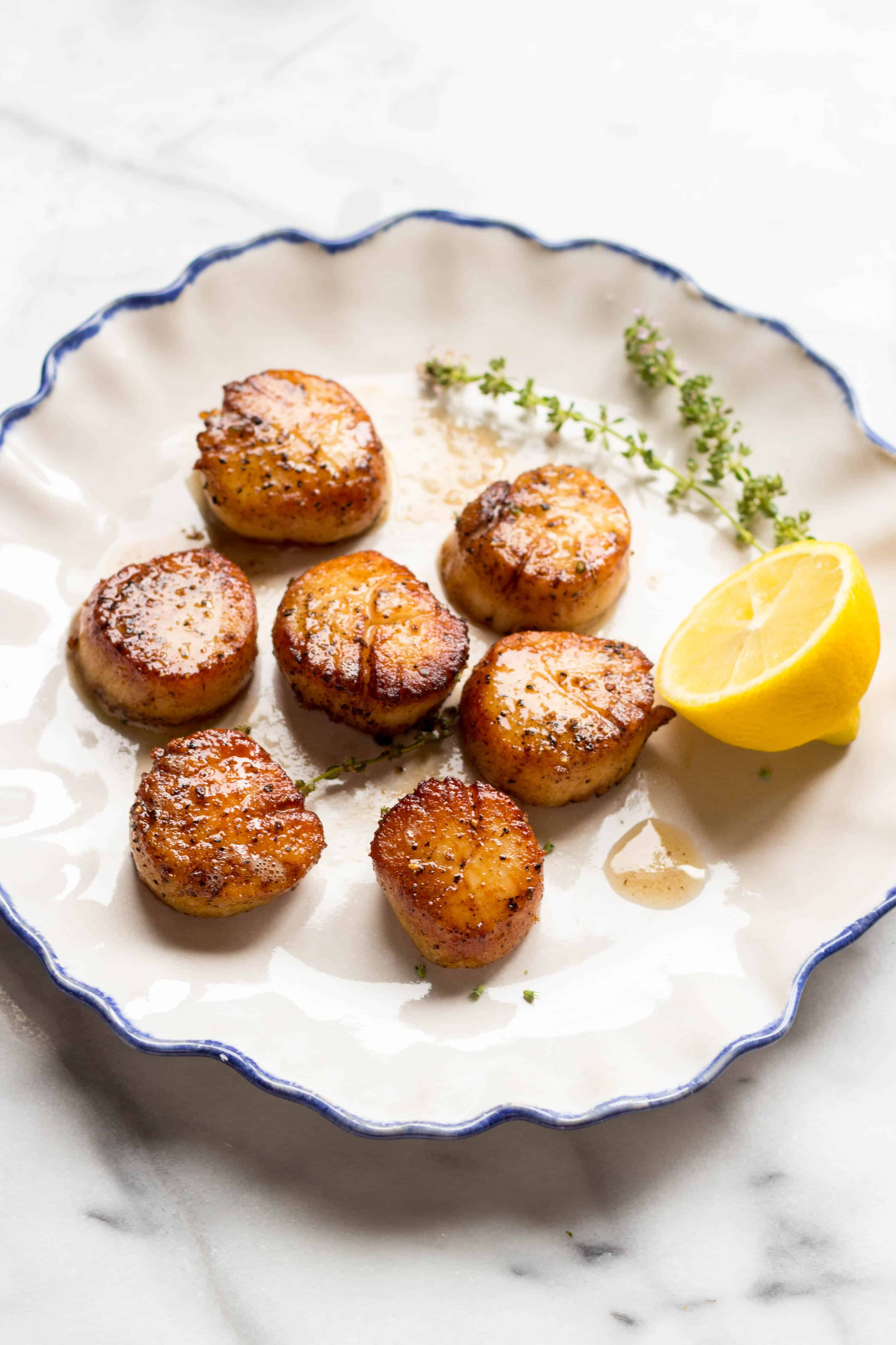 Blue edged white dinner plate with pan seared scallops and a lemon half.