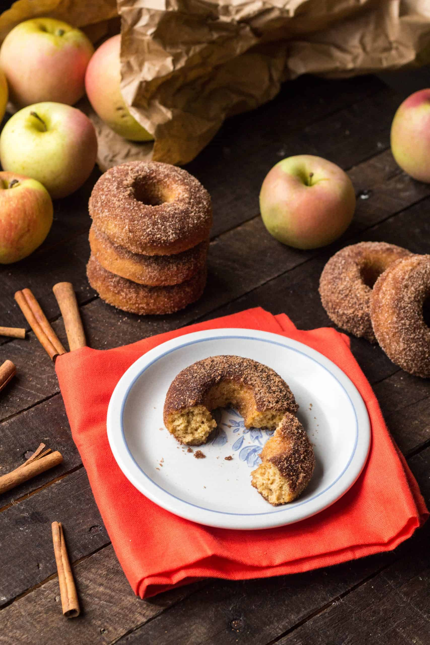 Broken apple cider doughnut on a gray plate with a red-orange napkin on a dark wood table with a stack of more doughnuts, apples, a brown paper bag and cinnamon sticks in the background