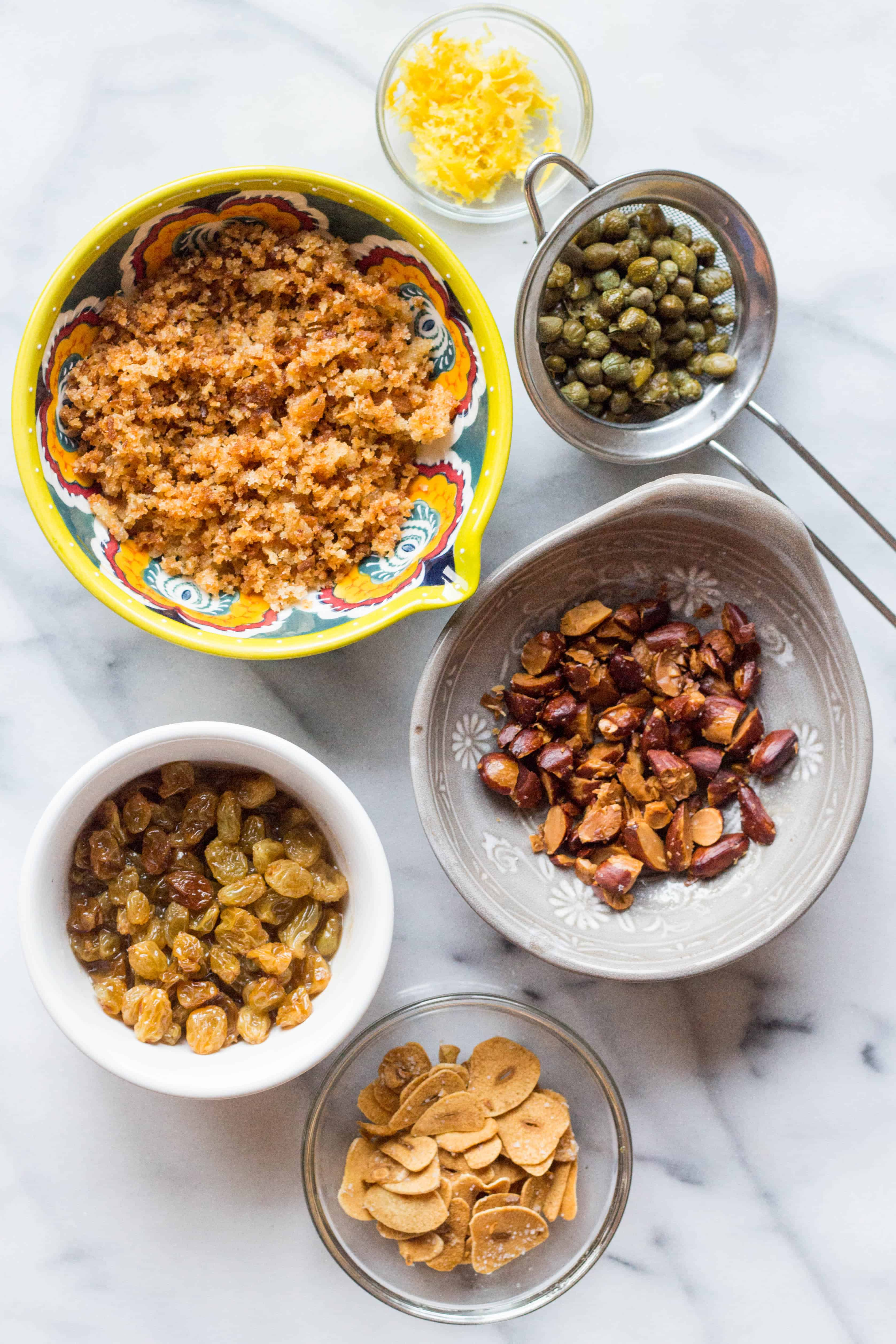 Several bowls on a marble counter filled with golden raisins, capers, toasted almonds, and capers.
