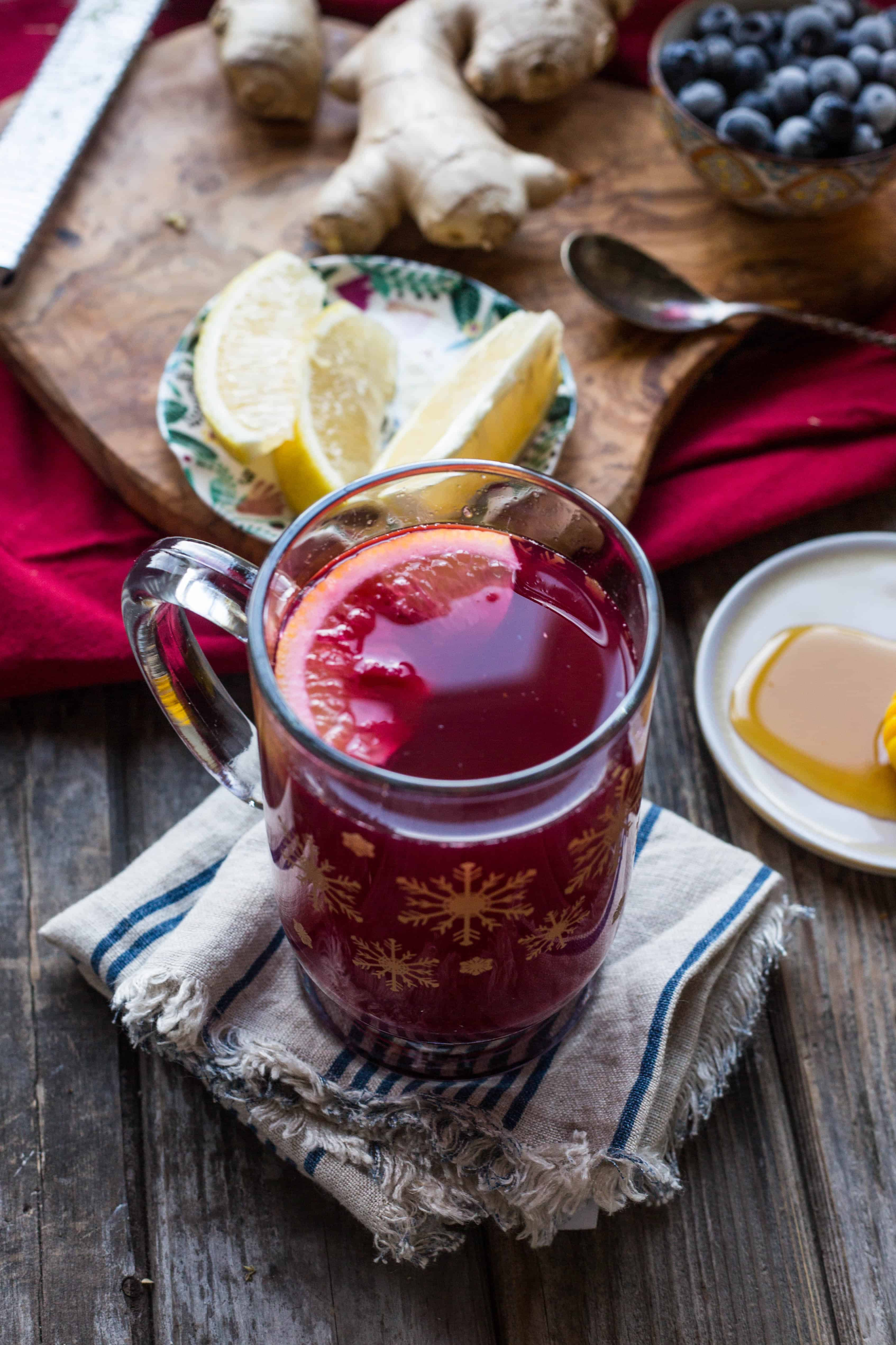 A mug of blueberry ginger hot toddy next to a plate of lemon wedges.