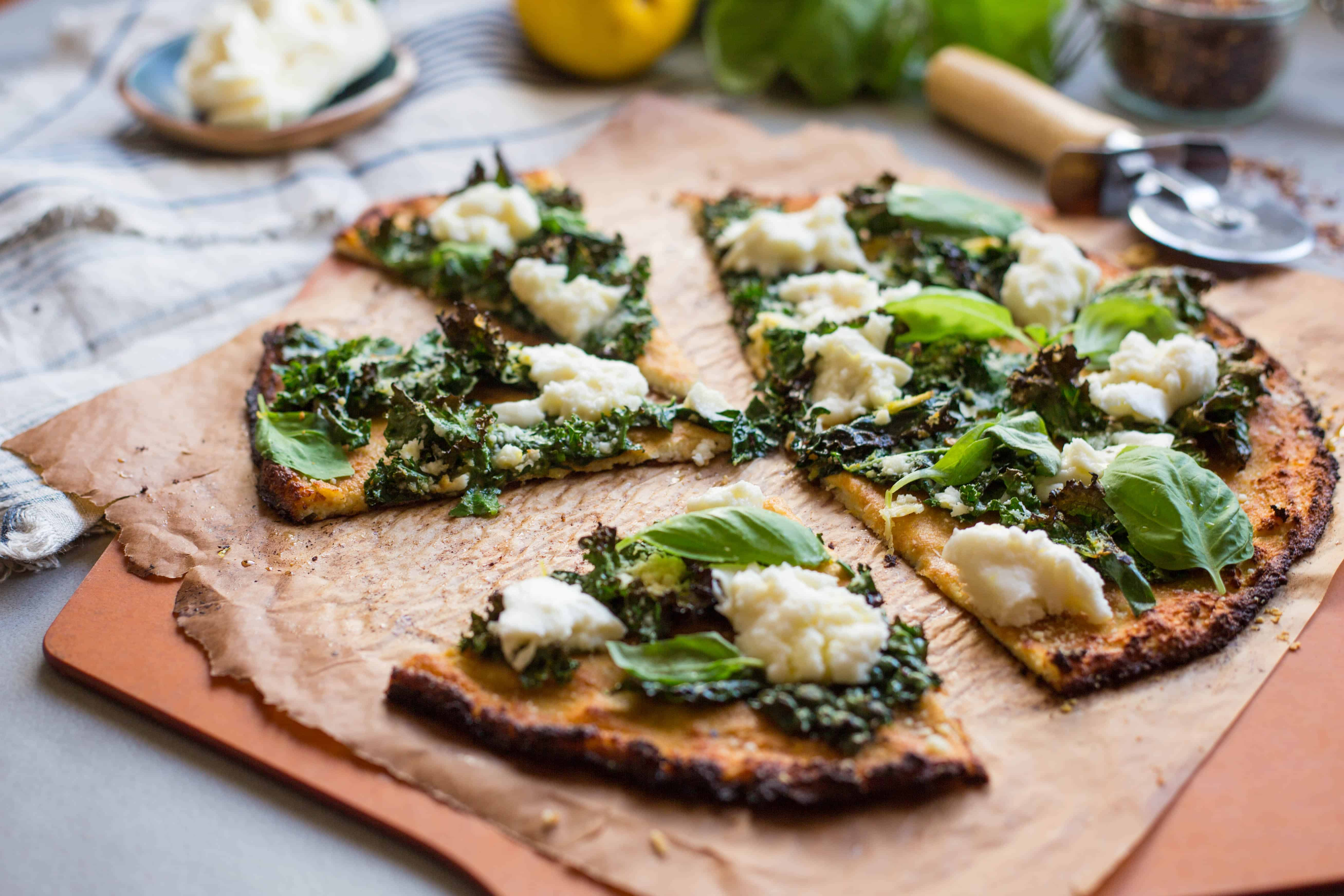 Cauliflower crust pizza topped with kale and mozzarella on a wood cutting board.