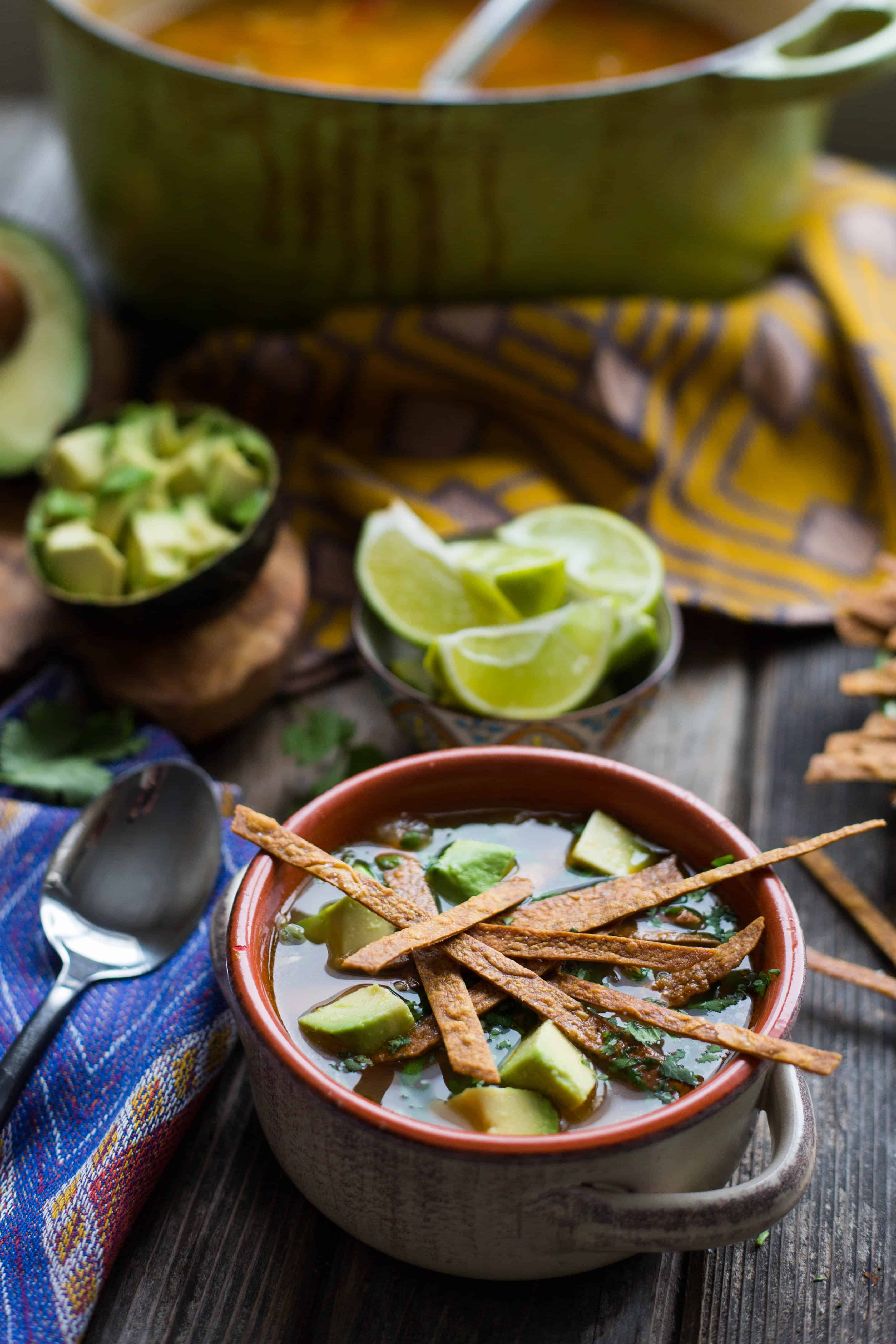A bowl of chicken tortilla soup set on a table with bowls of avocado and lime.
