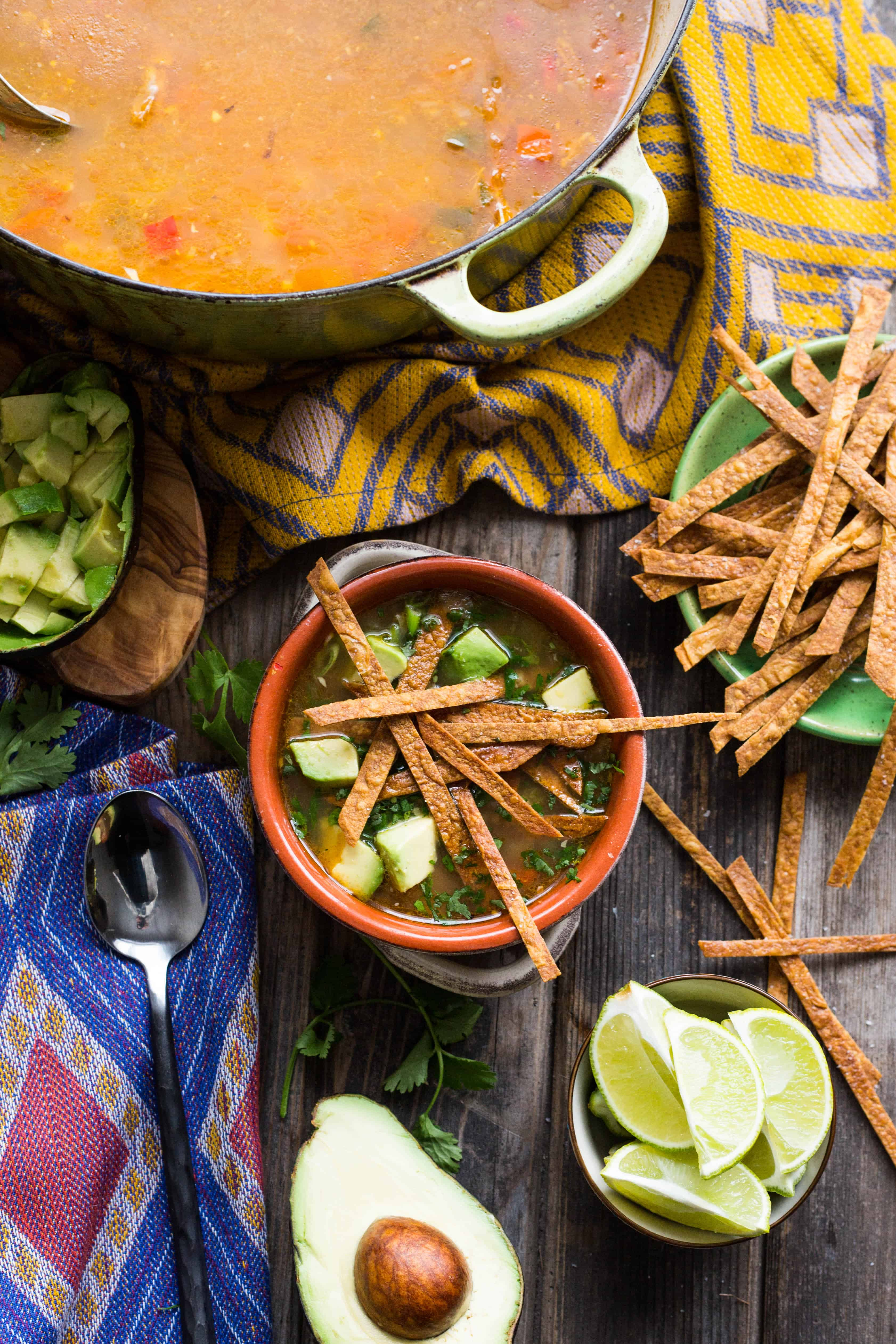Top view of a red earthenware bowl of tortilla soup topped with diced avocado and fried tortilla strips.