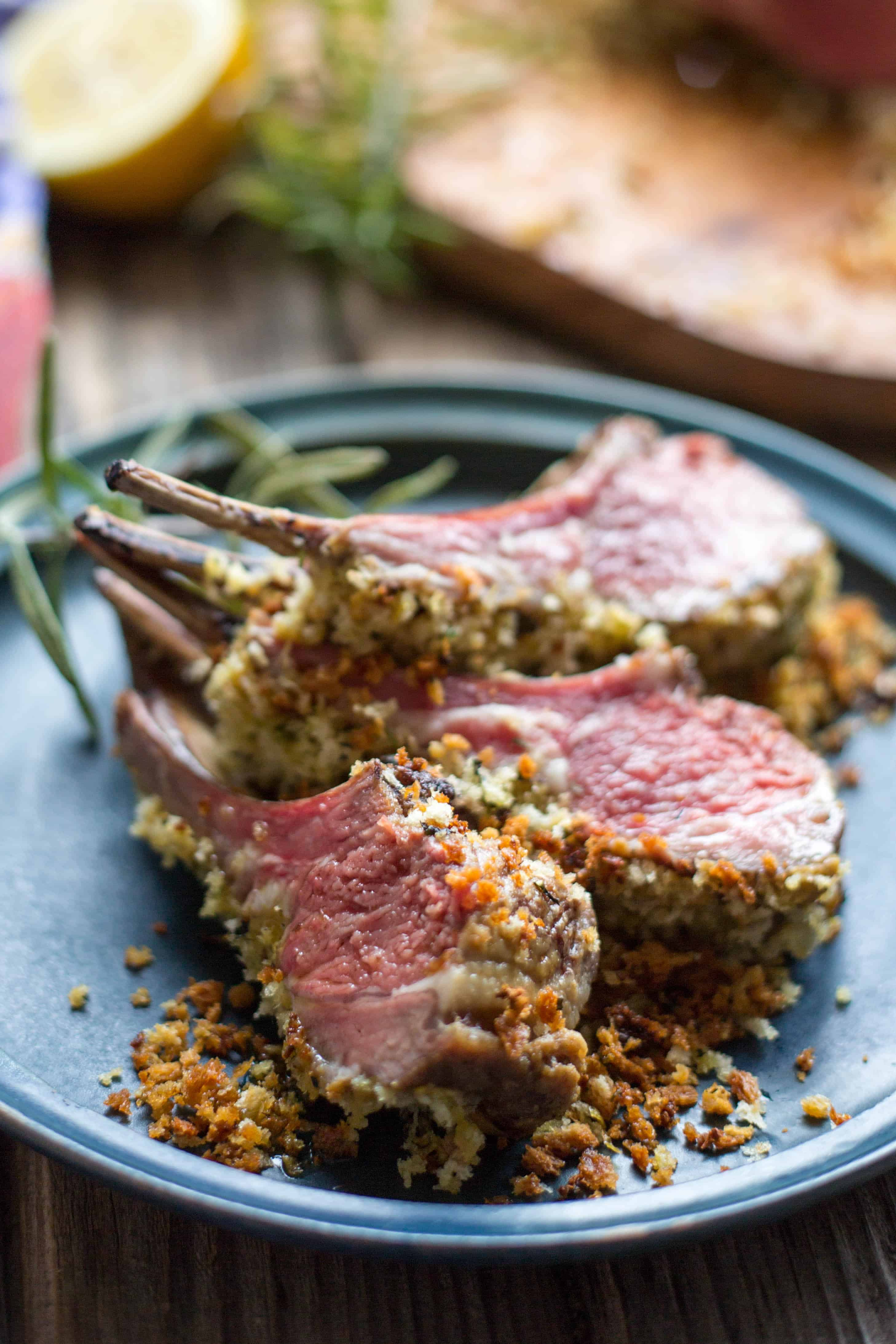 Three Dijon crusted lamb chops set on a blue dinner plate with a sprig of fresh rosemary.