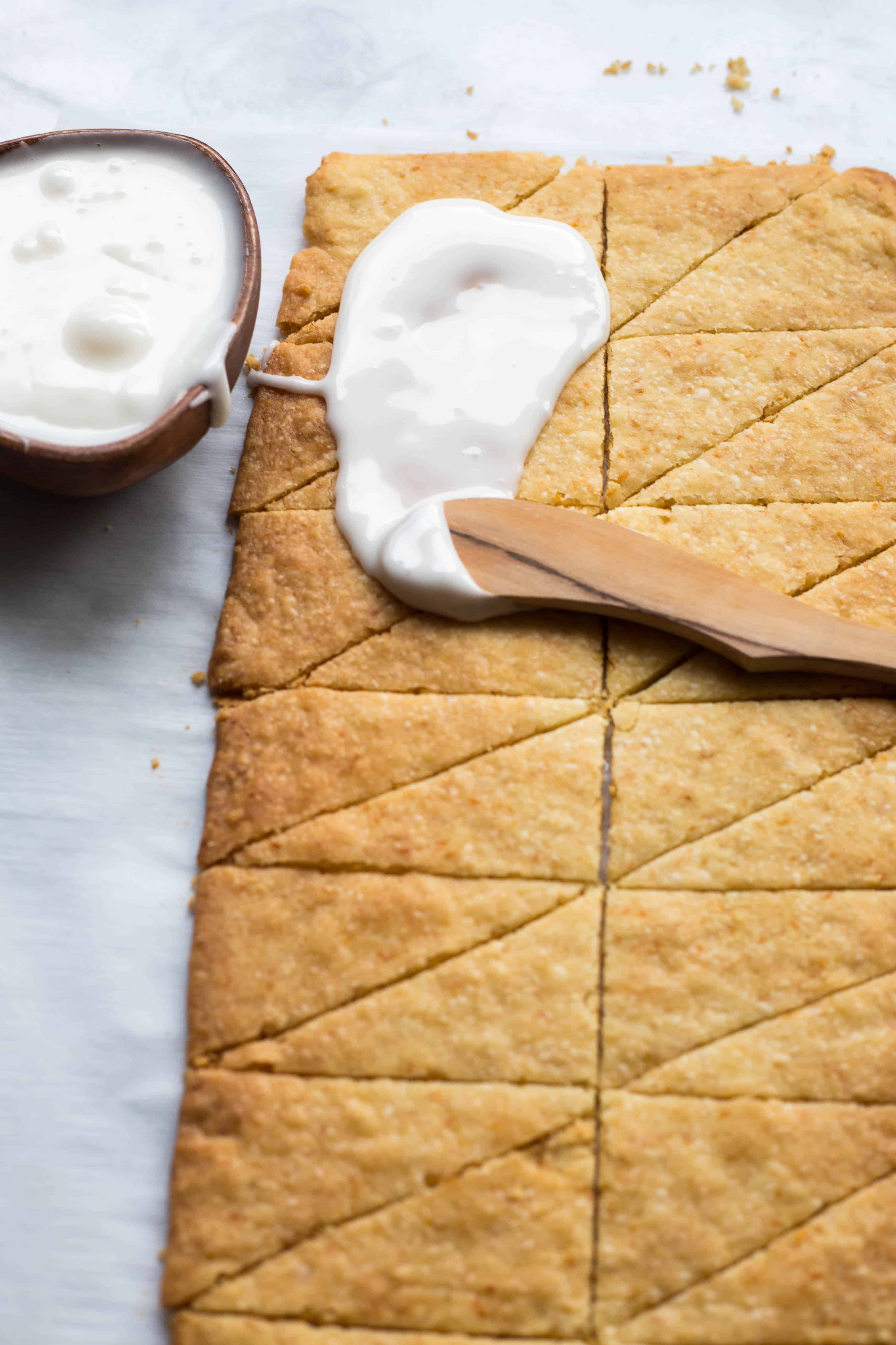 Spreading white icing on a sheet of baked shortbread cookies cut into triangles.