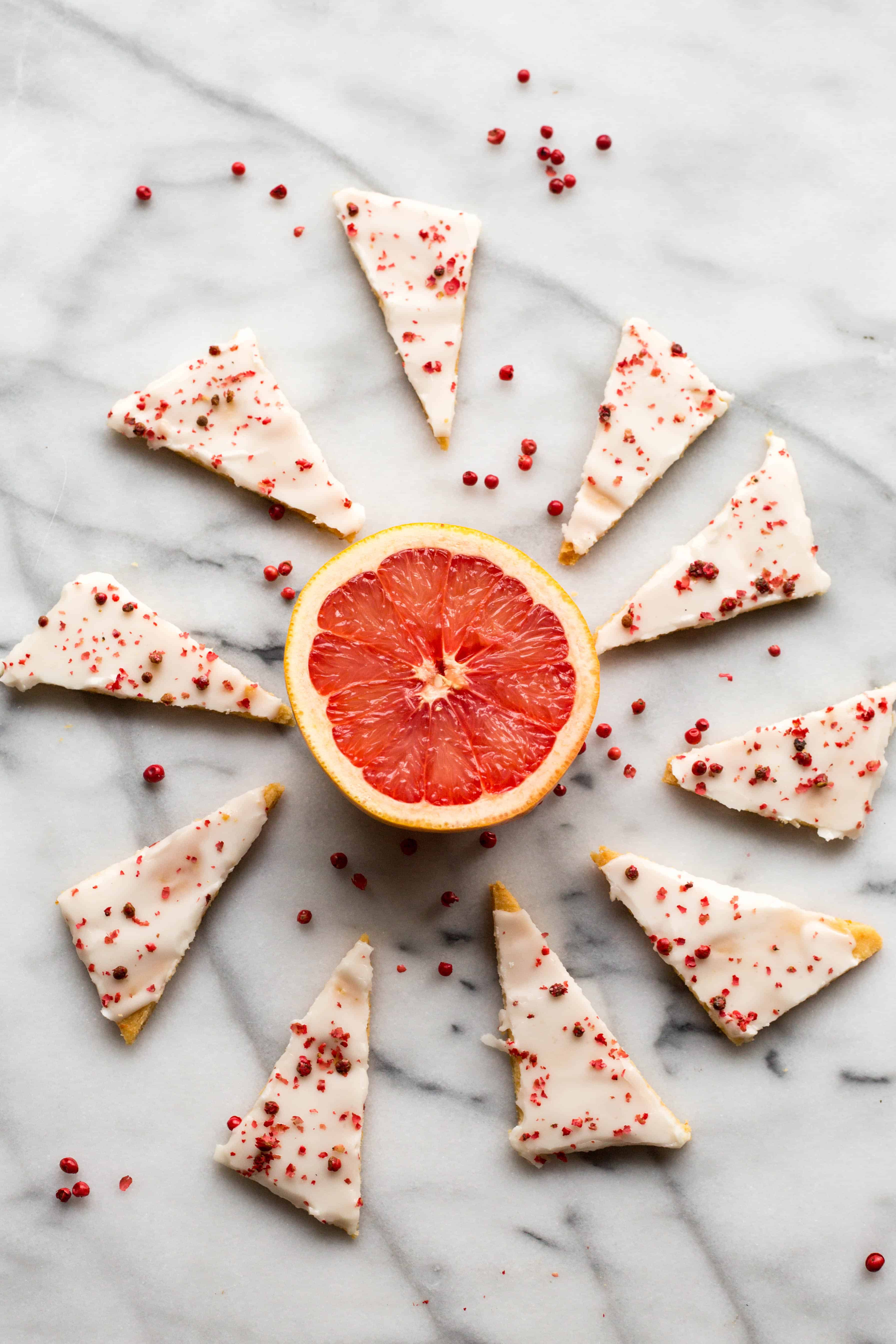 Triangles of grapefruit shortbread set out in an array around a grapefruit half.