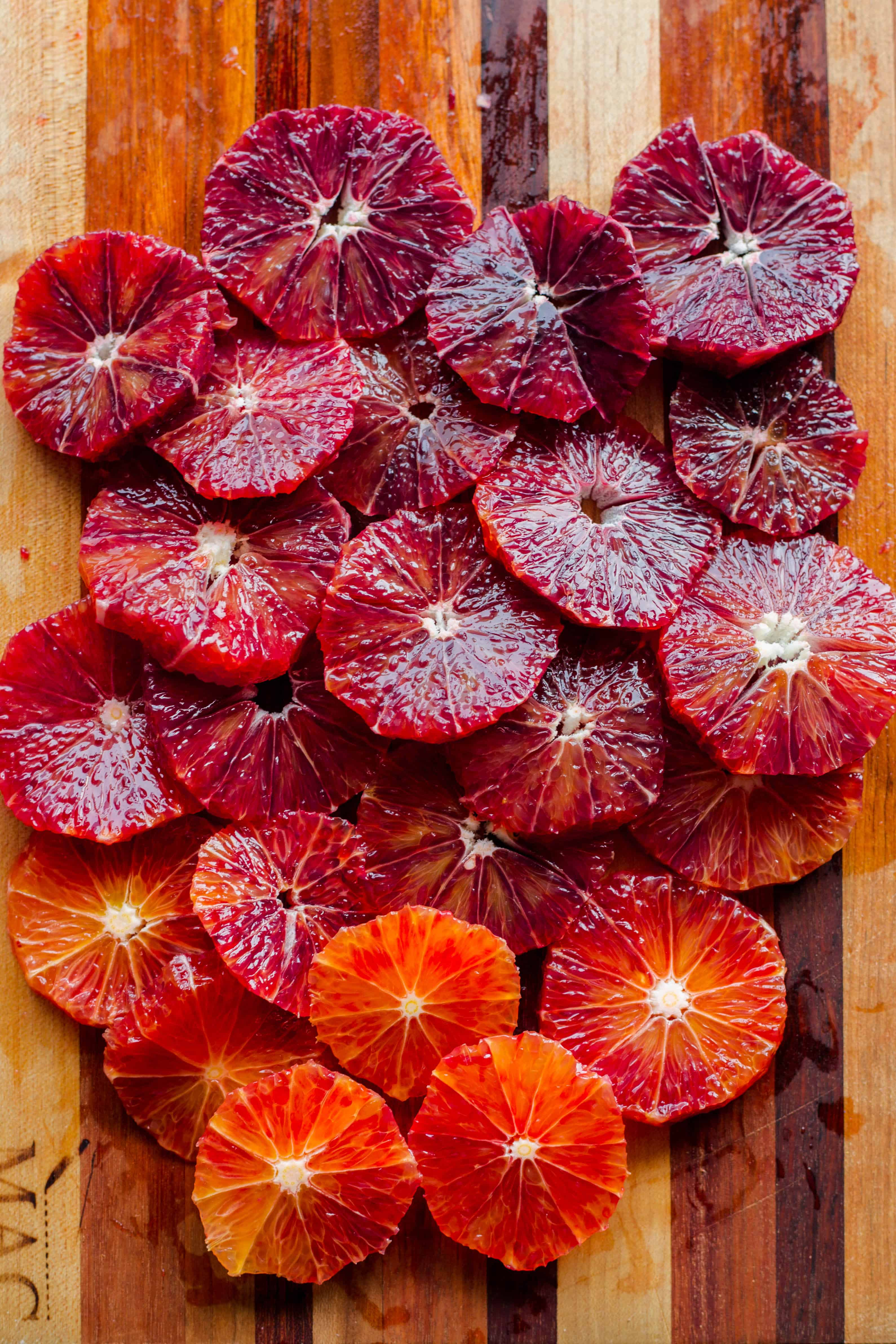 Thin cross sections of blood oranges covering a wood cutting board.