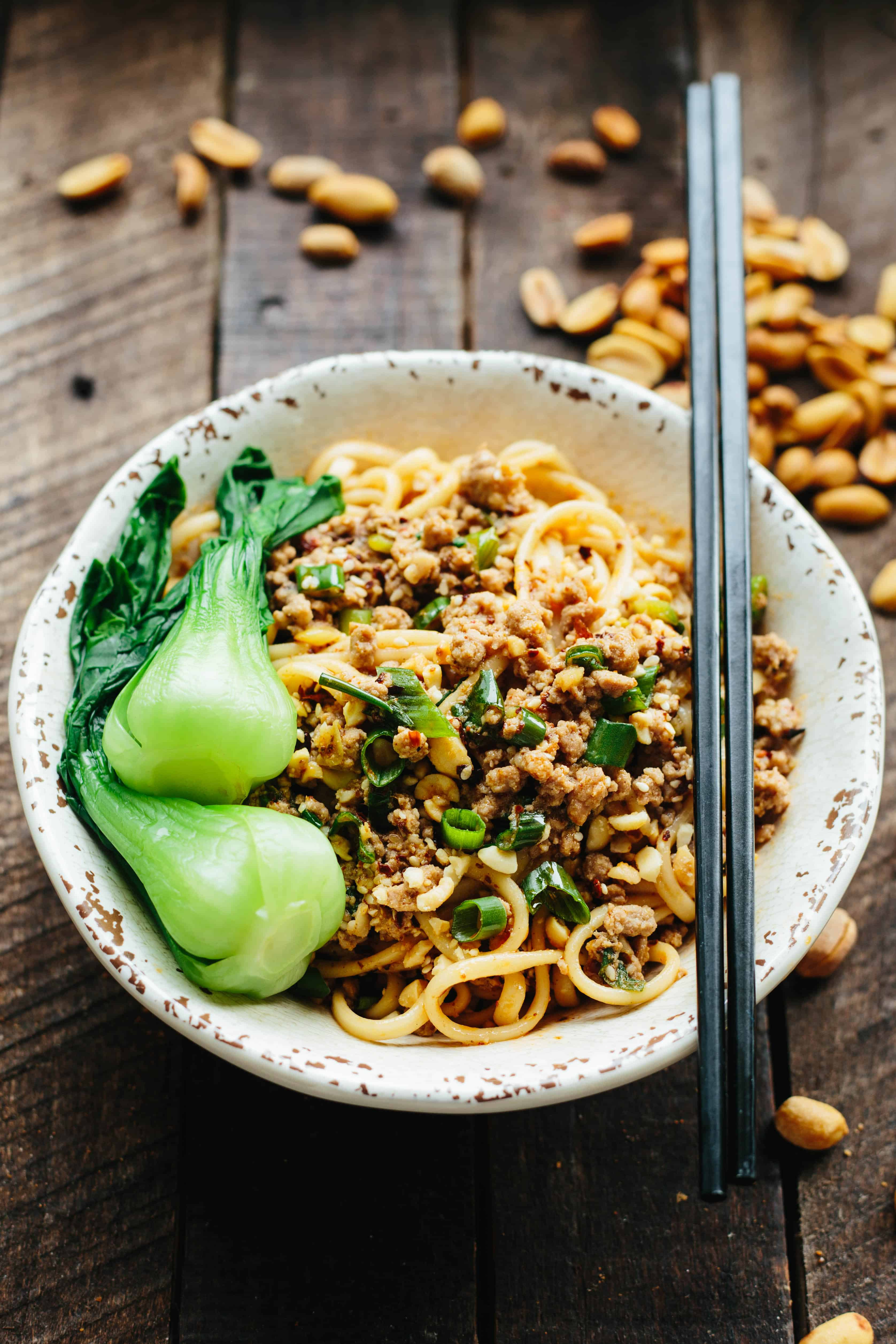 A white bowl filled with dan dan noodles and baby bok choy with chopsticks resting across the top.