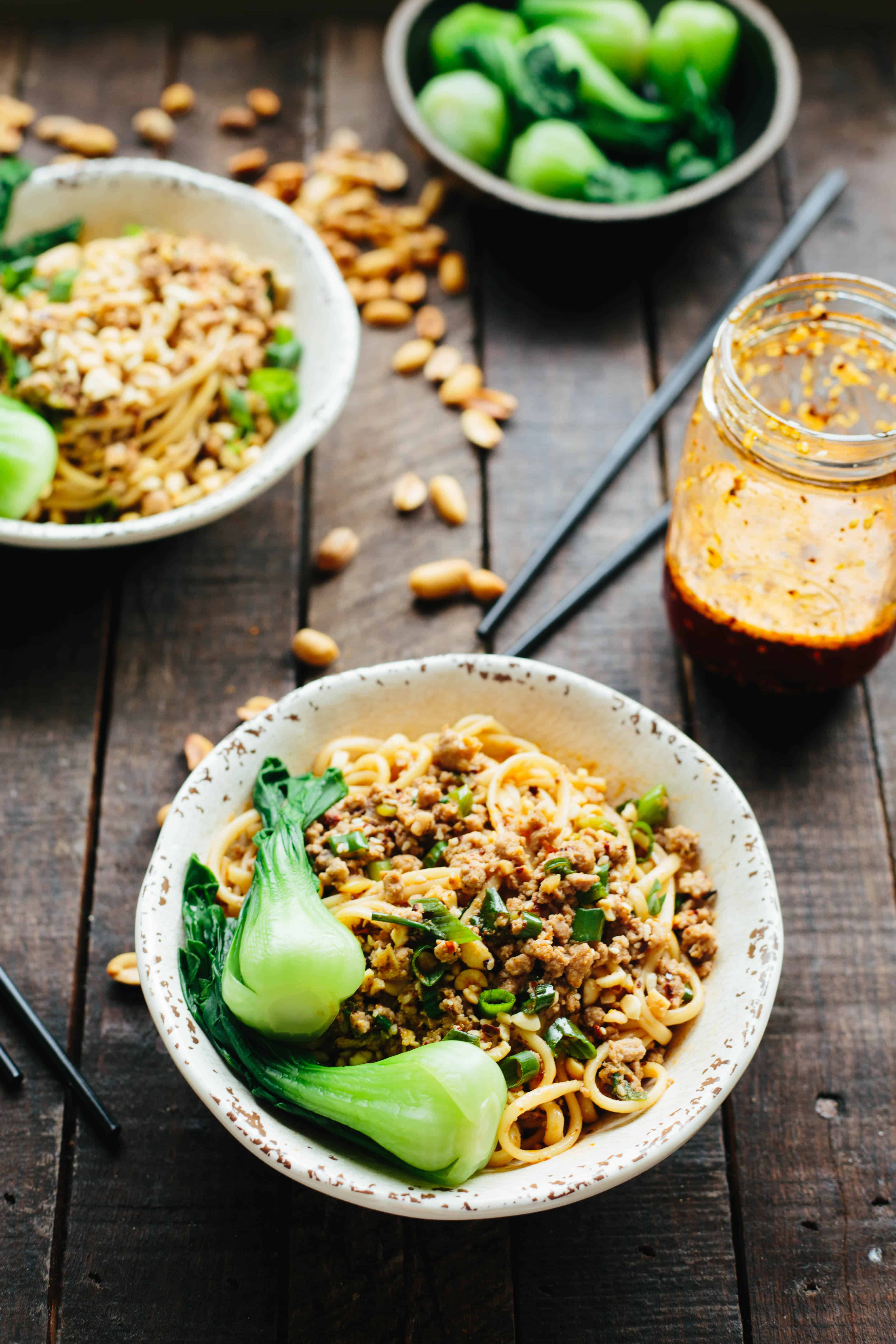 Two bowls of dan dan noodles and a glass jar of homemade chili oil.