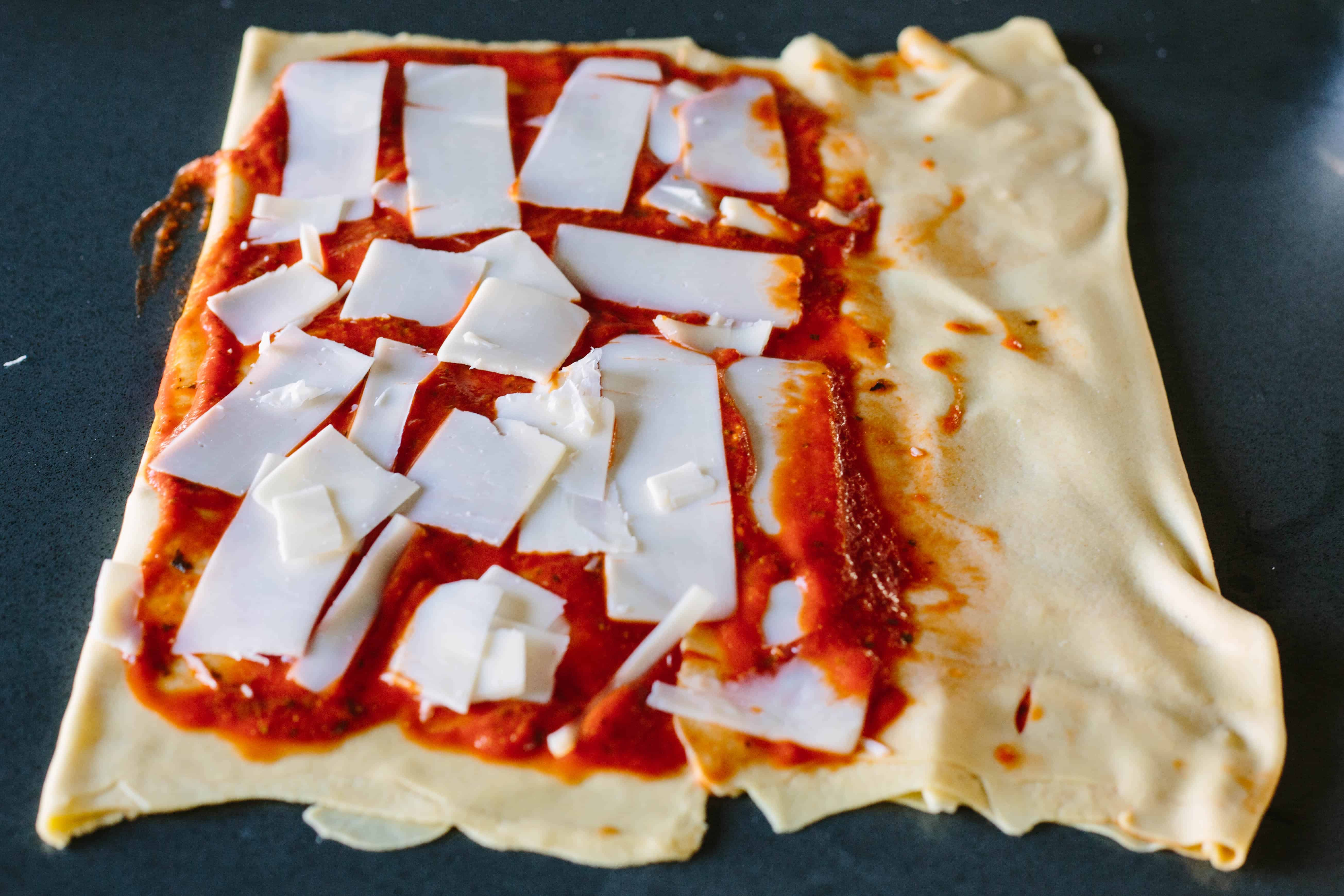 Folding bread dough over layers of cheese and pizza sauce.