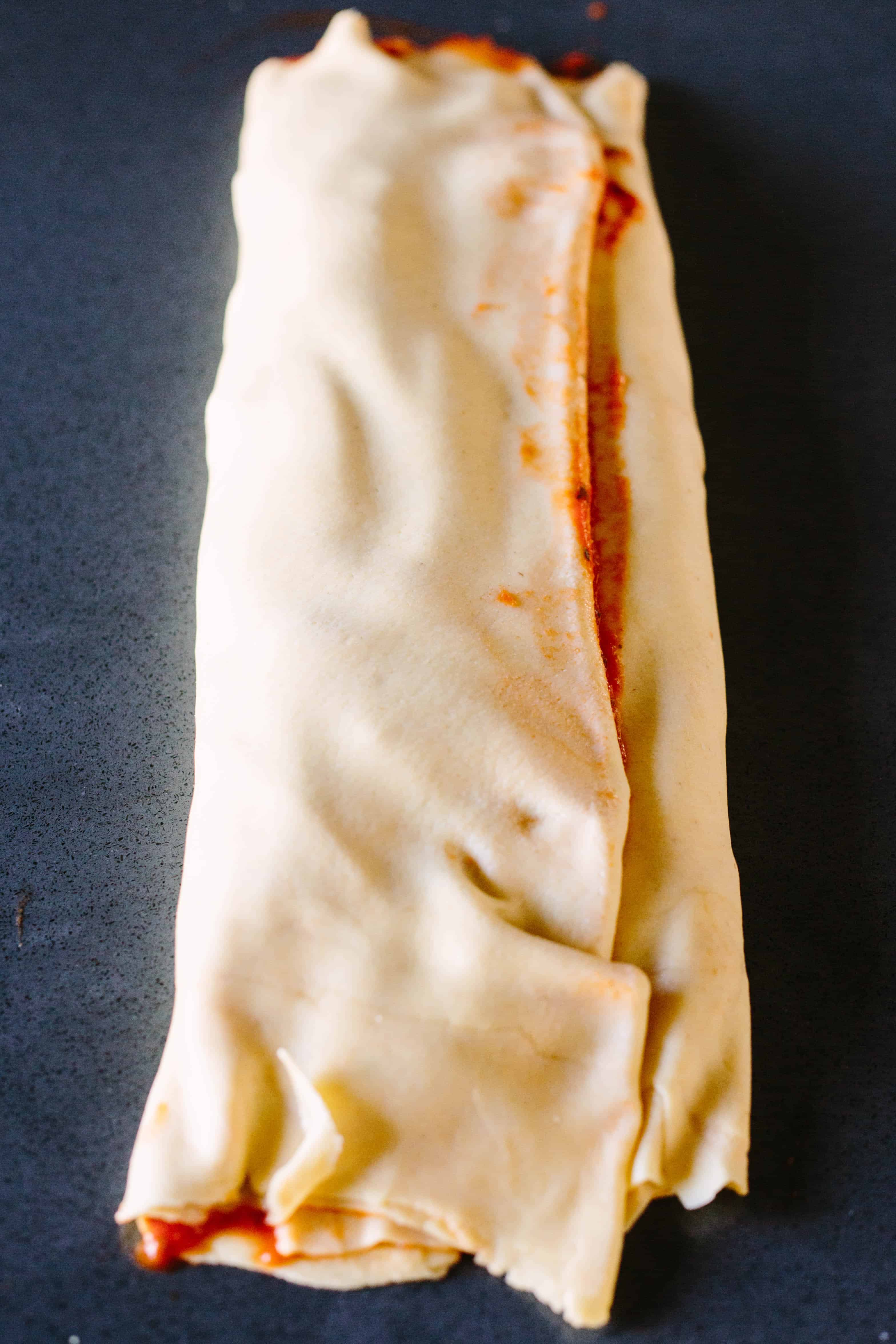Folding up bread dough layered with cheese and pizza sauce like an envelope.