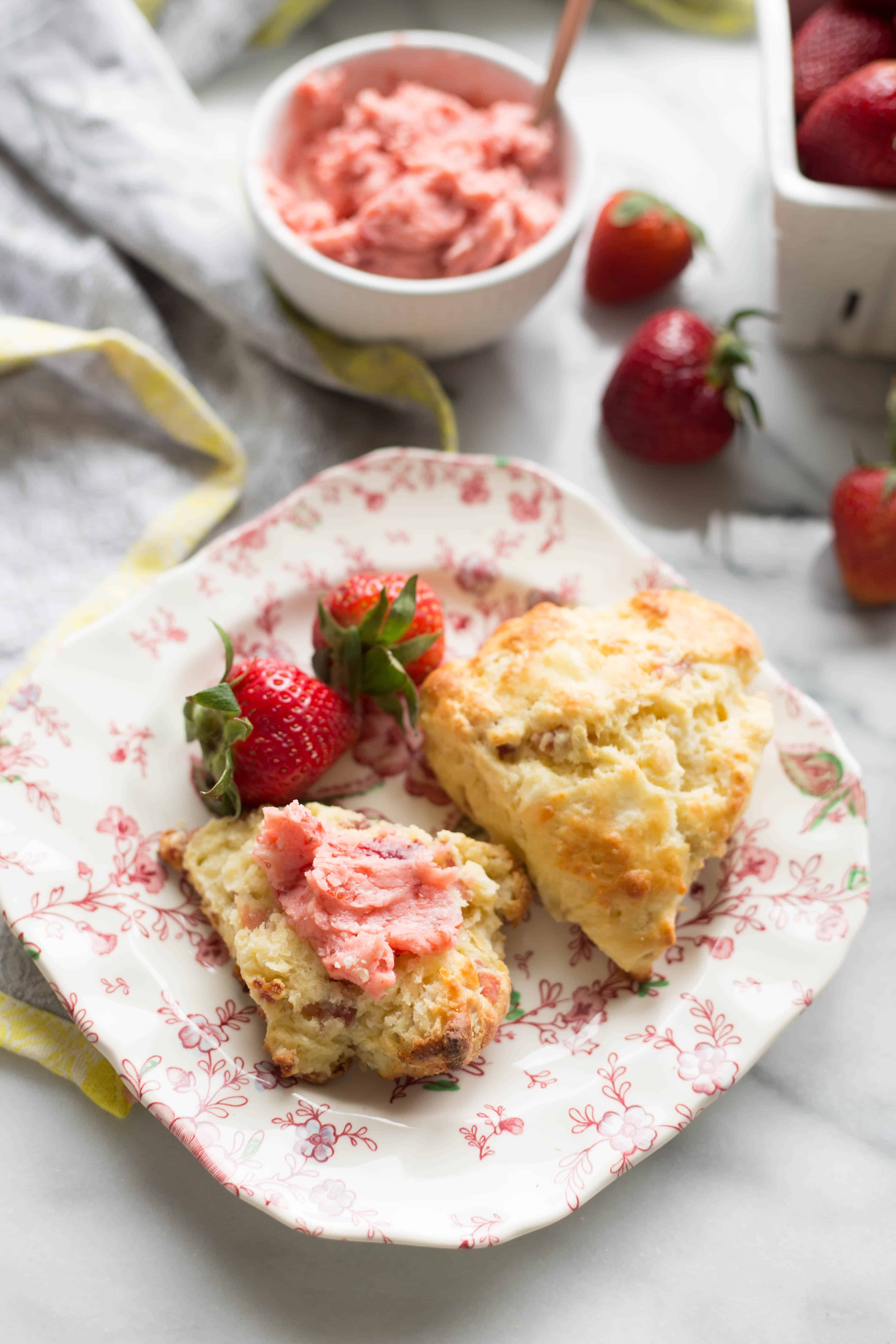 Square floral plate with two scones and fresh whole strawberries.