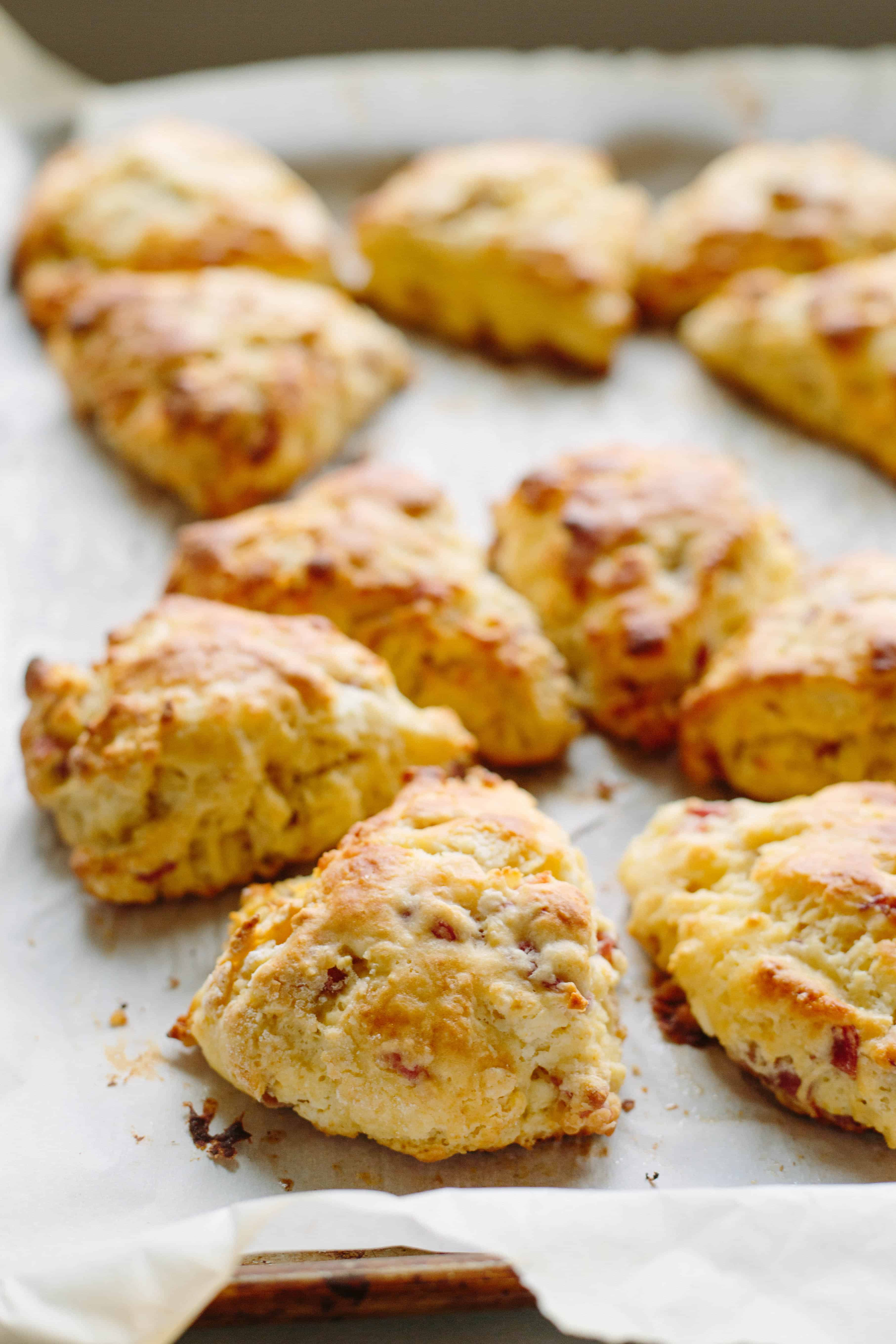 Freshly baked prosciutto goat cheese scones on a baking sheet.